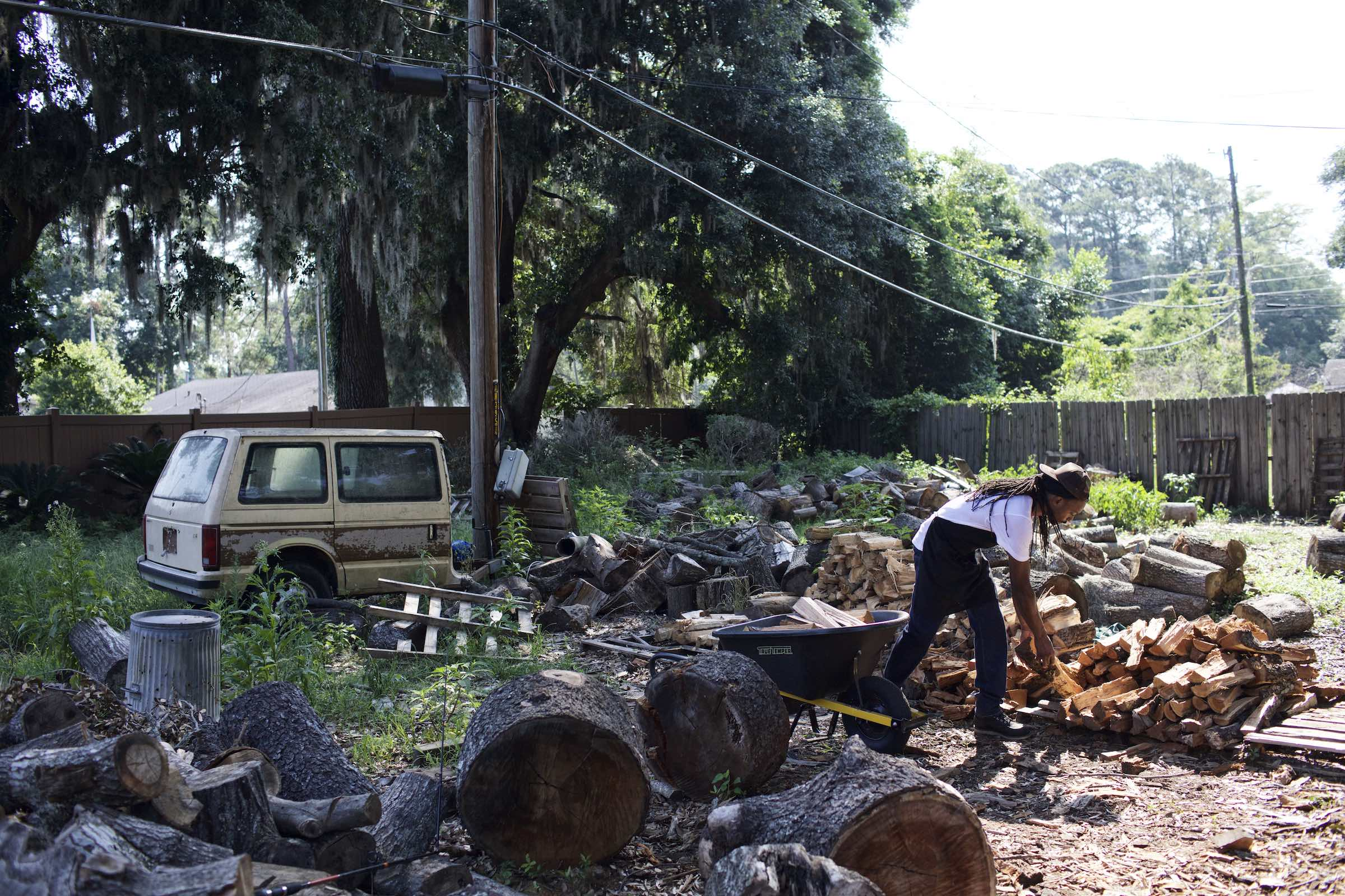 Jody Horton Photography - Chef chopping and piling wood in a lush yet disheveled yard.