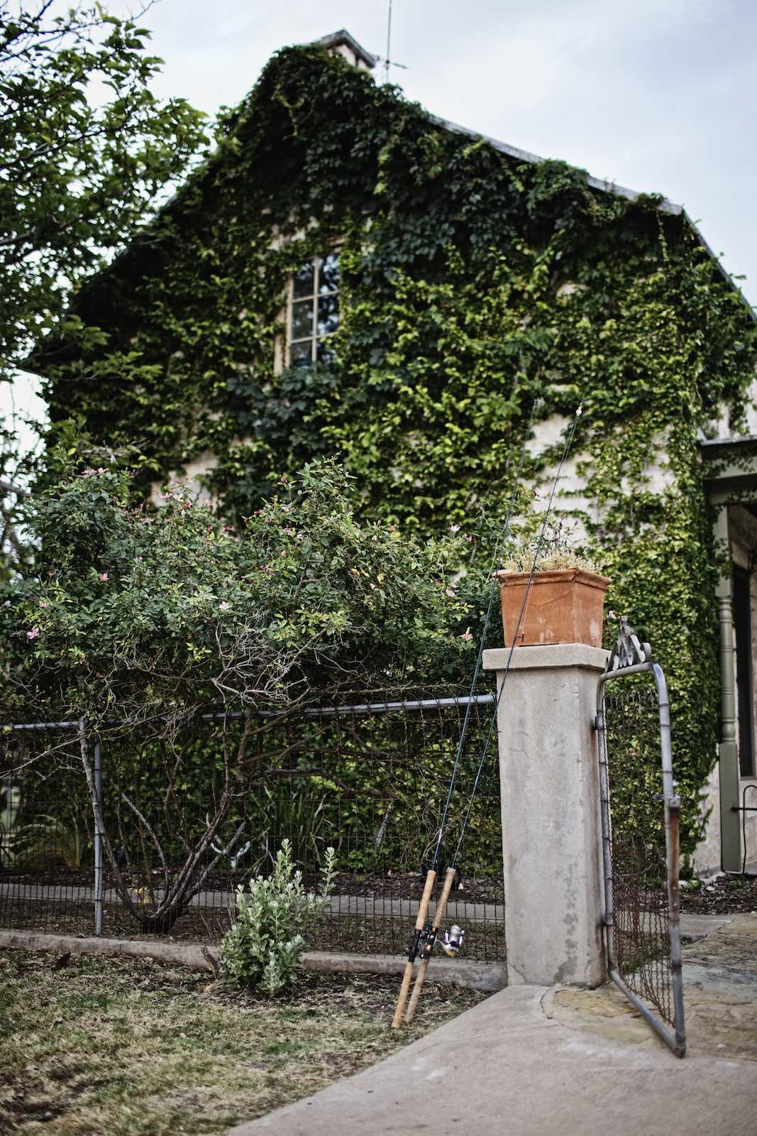 Jody Horton Photography - Fishing rods in front of a vine-covered cottage.