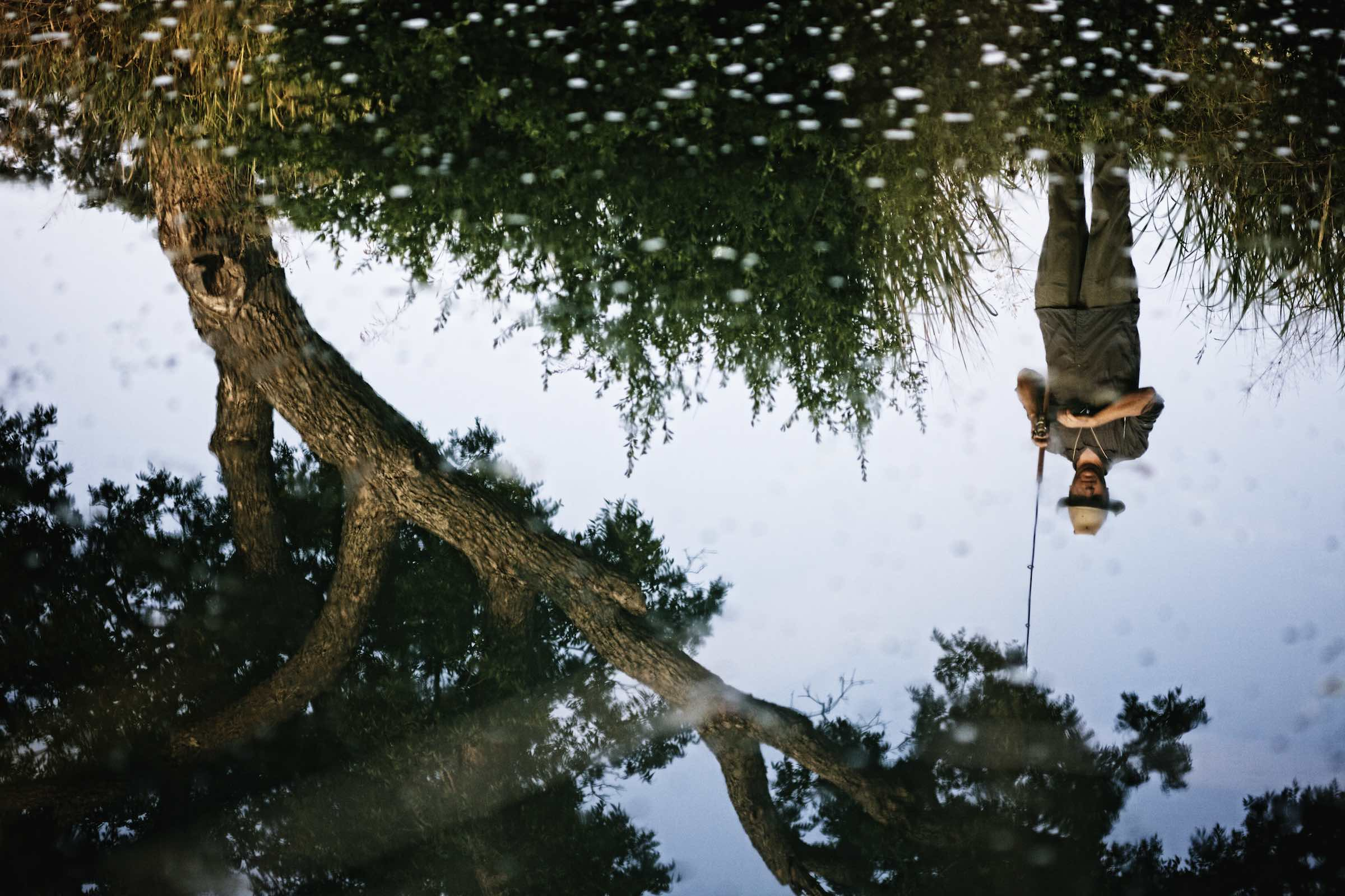 Jody Horton Photography - Inverted reflection of a fisherman on the water.