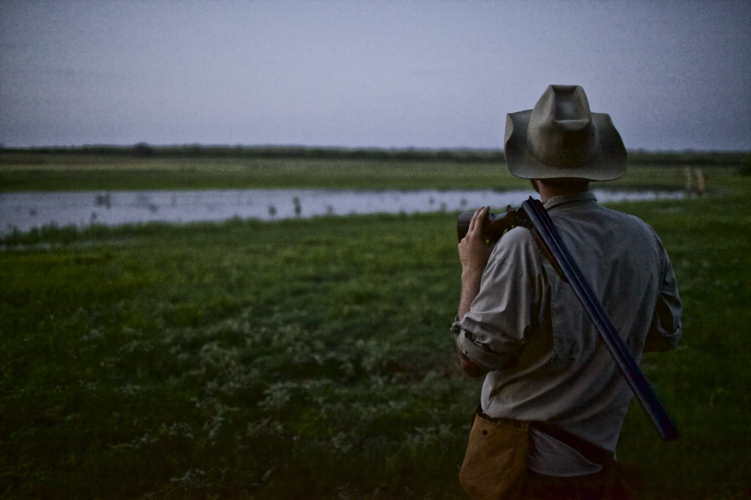 Jody Horton Photography - Hunter facing an open field with his rifle over his shoulder.