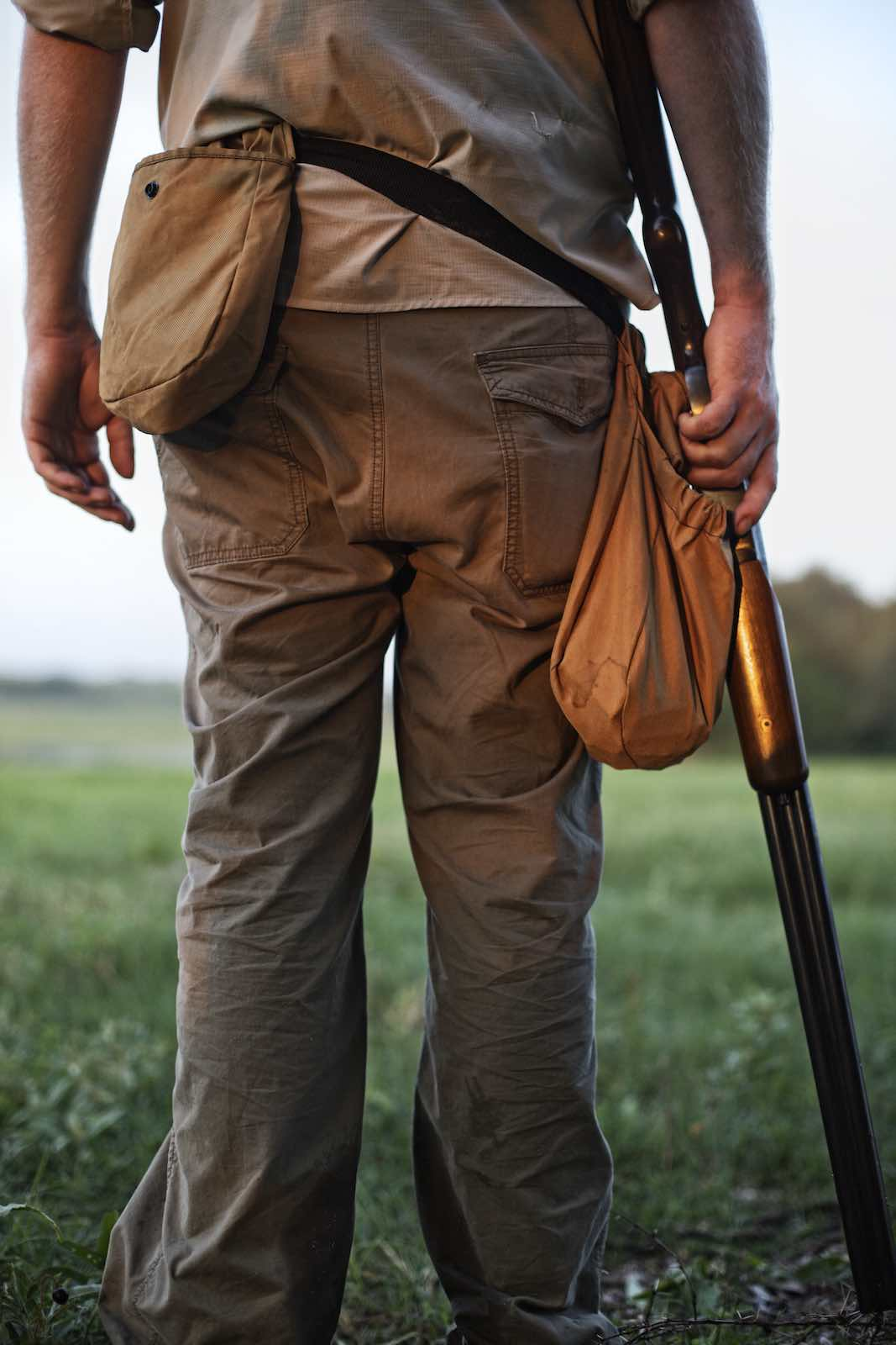Jody Horton Photography - Hunter standing in grass with his rifle beside his leg.