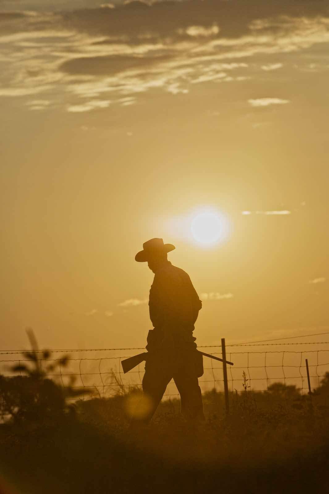 Jody Horton Photography - Hunter walking next to a wire fence at sundown.