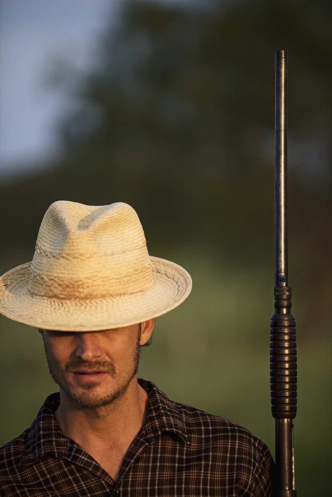 Jody Horton Photography - Hunter is a straw hat carrying his rifle parallel to his body.