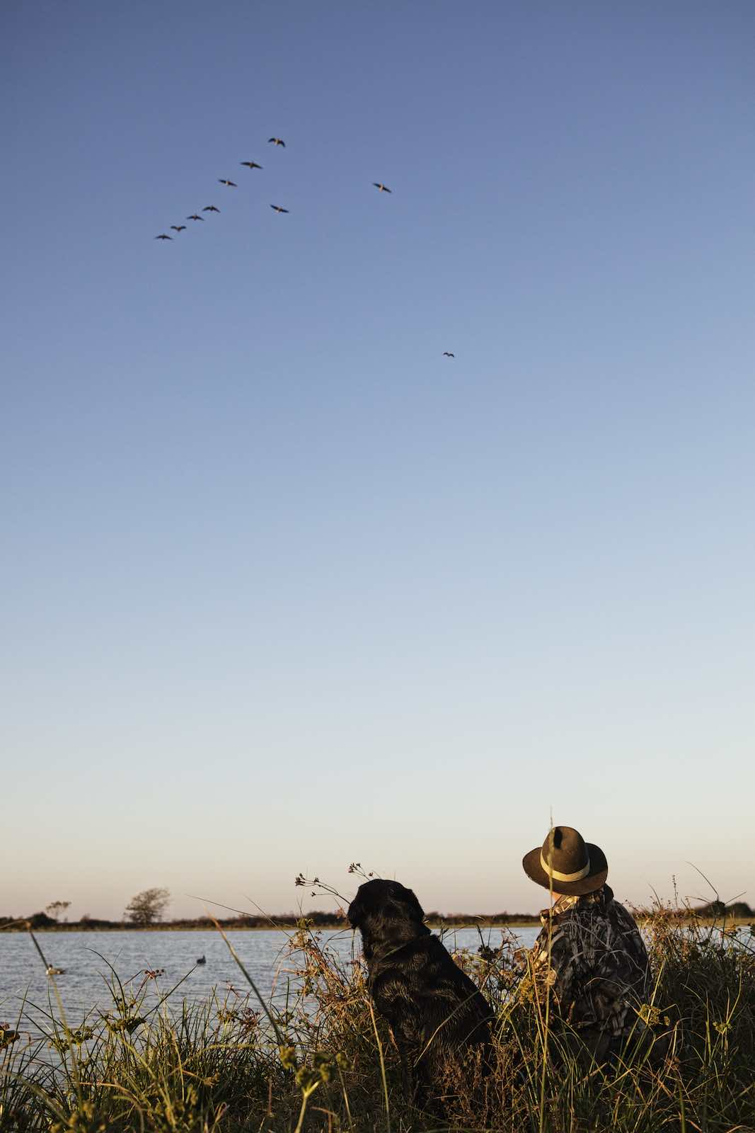 Jody Horton Photography - Hunter and his dog watching ducks fly above a lake.