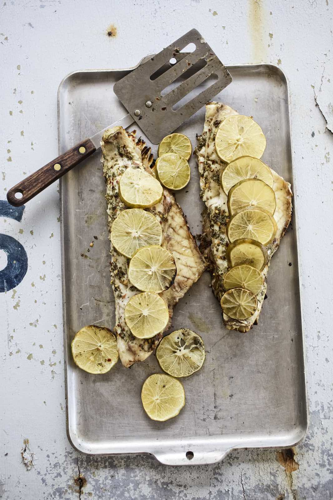 Jody Horton Photography - Grilled fish fillets with sliced lime on a metal sheet pan.