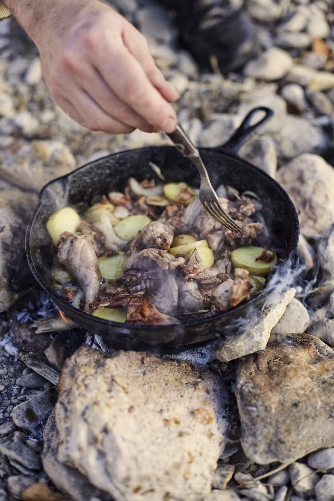 Jody Horton Photography - Meats and vegetables cooking in a cast iron skillet on an camp fire.