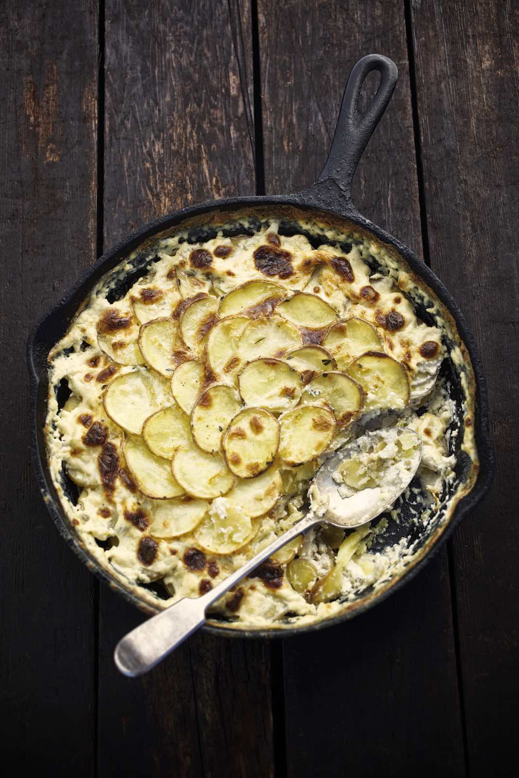 Jody Horton Photography - Potatoes Au Gratin in cast iron skillet on wood picnic table.