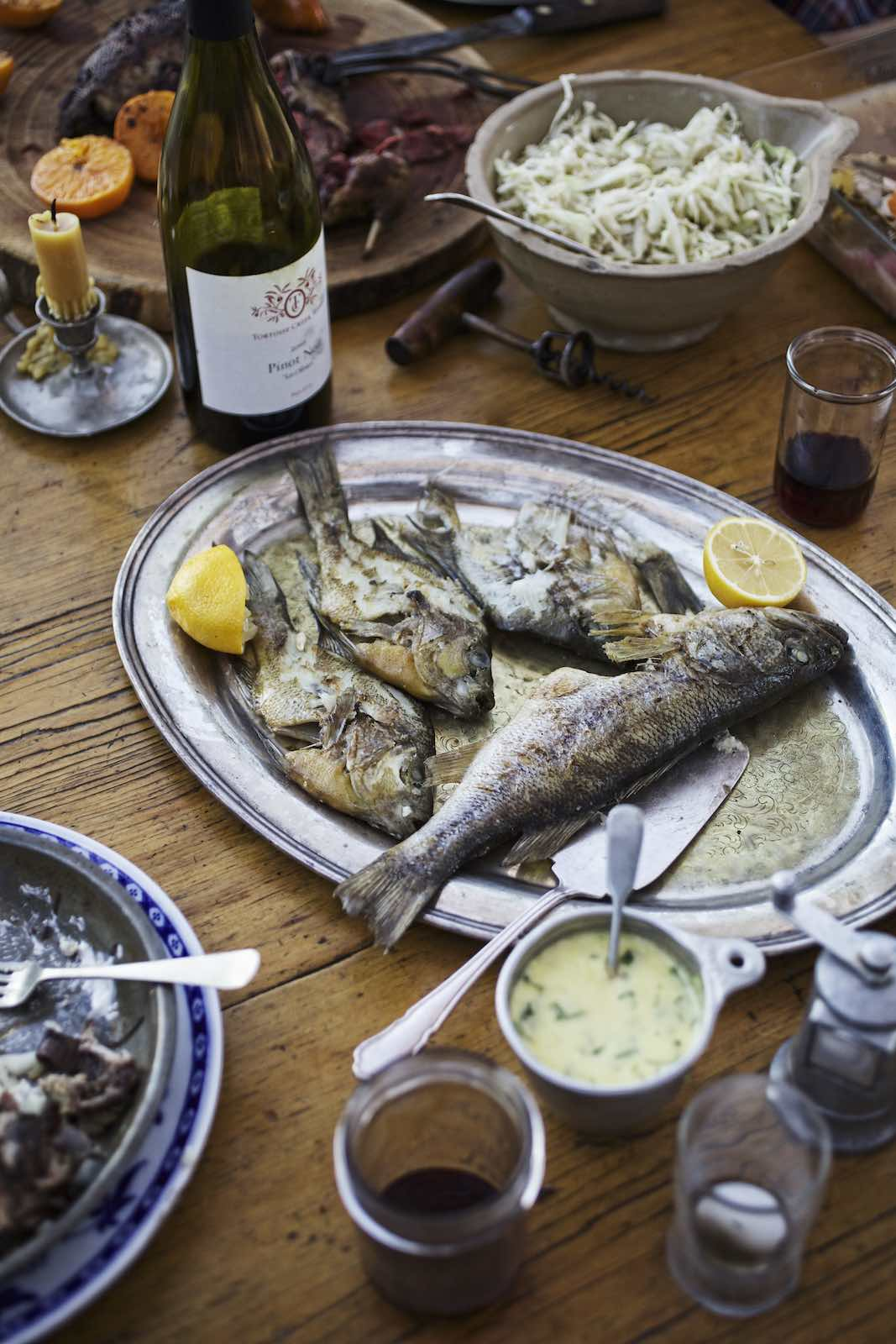 Jody Horton Photography - Whole cooked fish among a sprawling dinner spread.