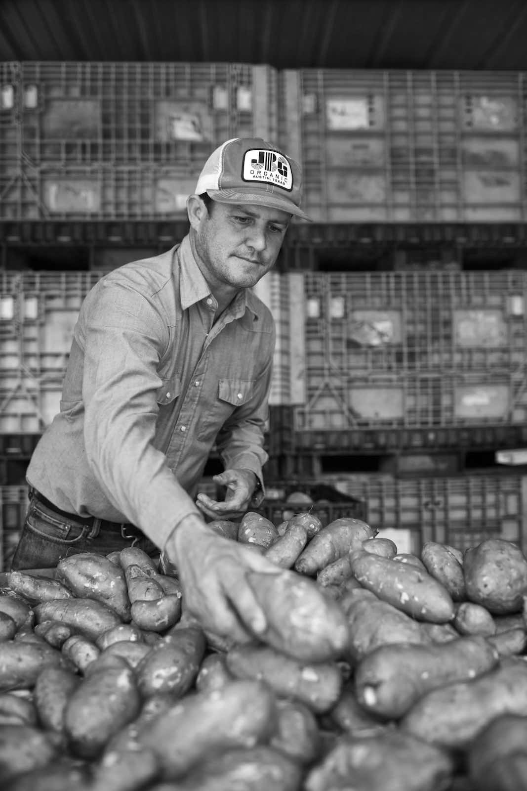 Jody Horton Photography - Farmer handling a haul of sweet potatoes, shot in B&W.