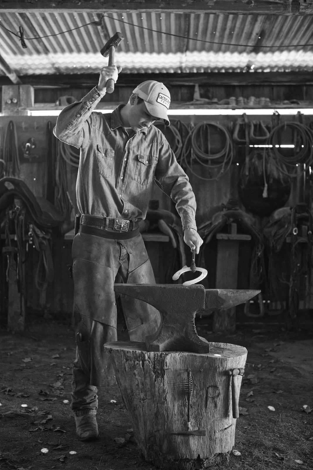 Jody Horton Photography - Welder hammering a horseshoe in a covered barn, shot in B&W.