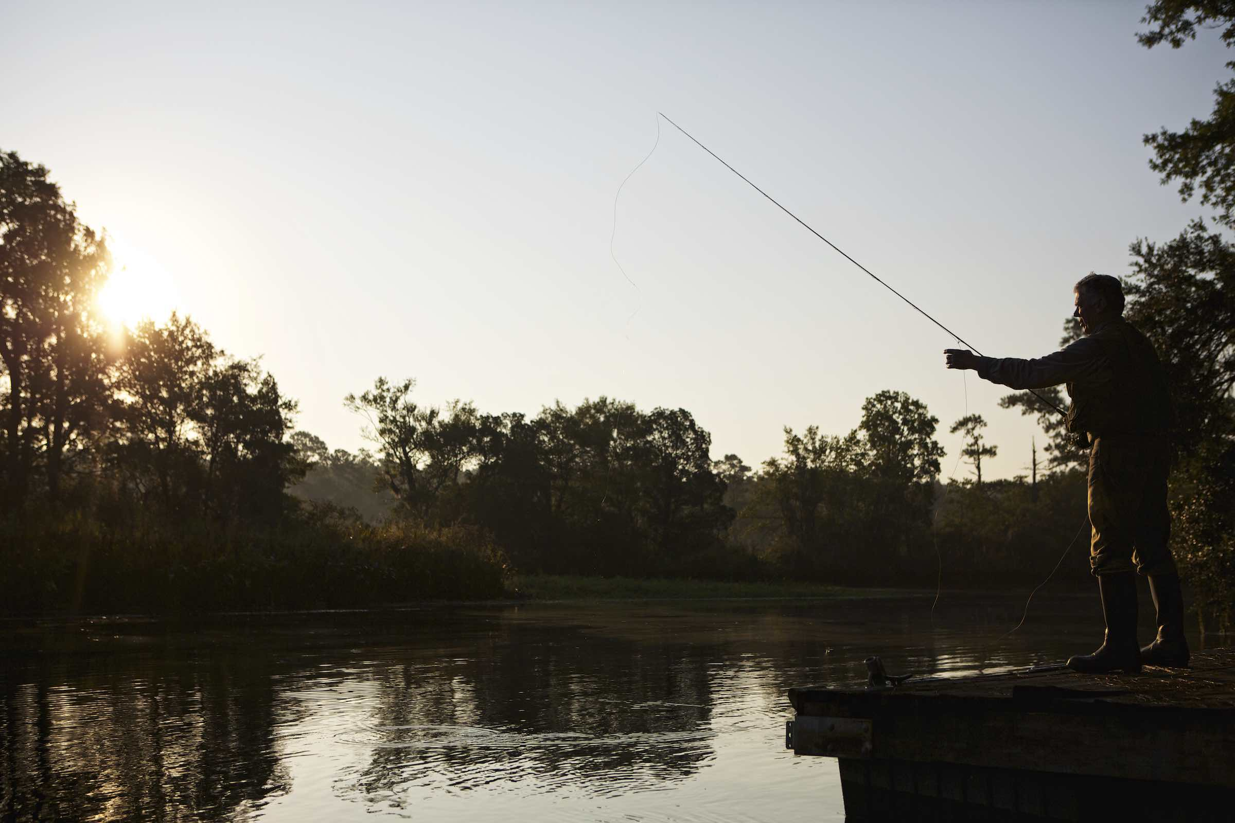 Jody Horton Photography - Fisherman standing on a dock at sunset while casting a line into the river.
