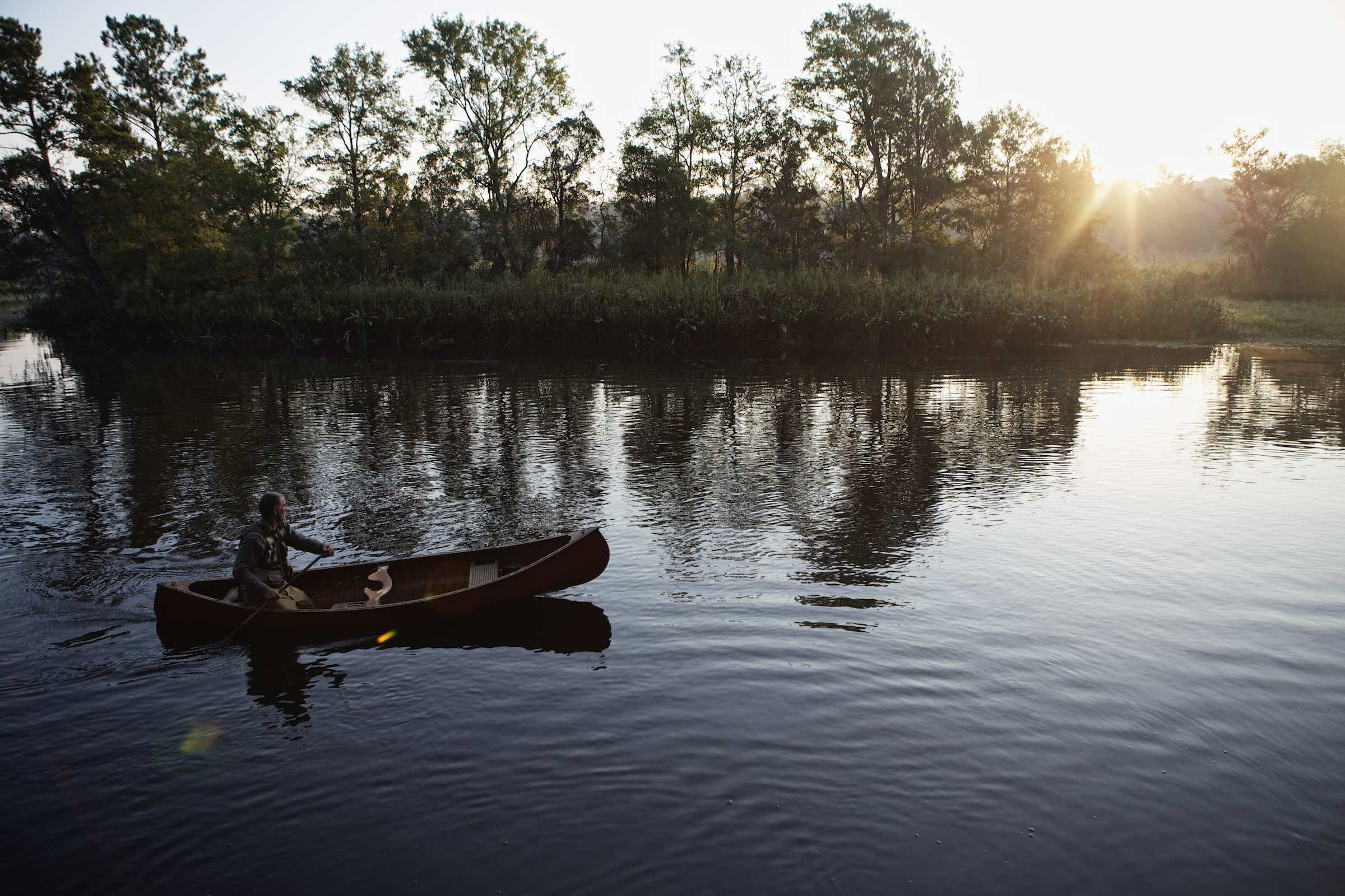Jody Horton Photography - Canoer sitting in a wood canoe gliding through still waters at sunset.
