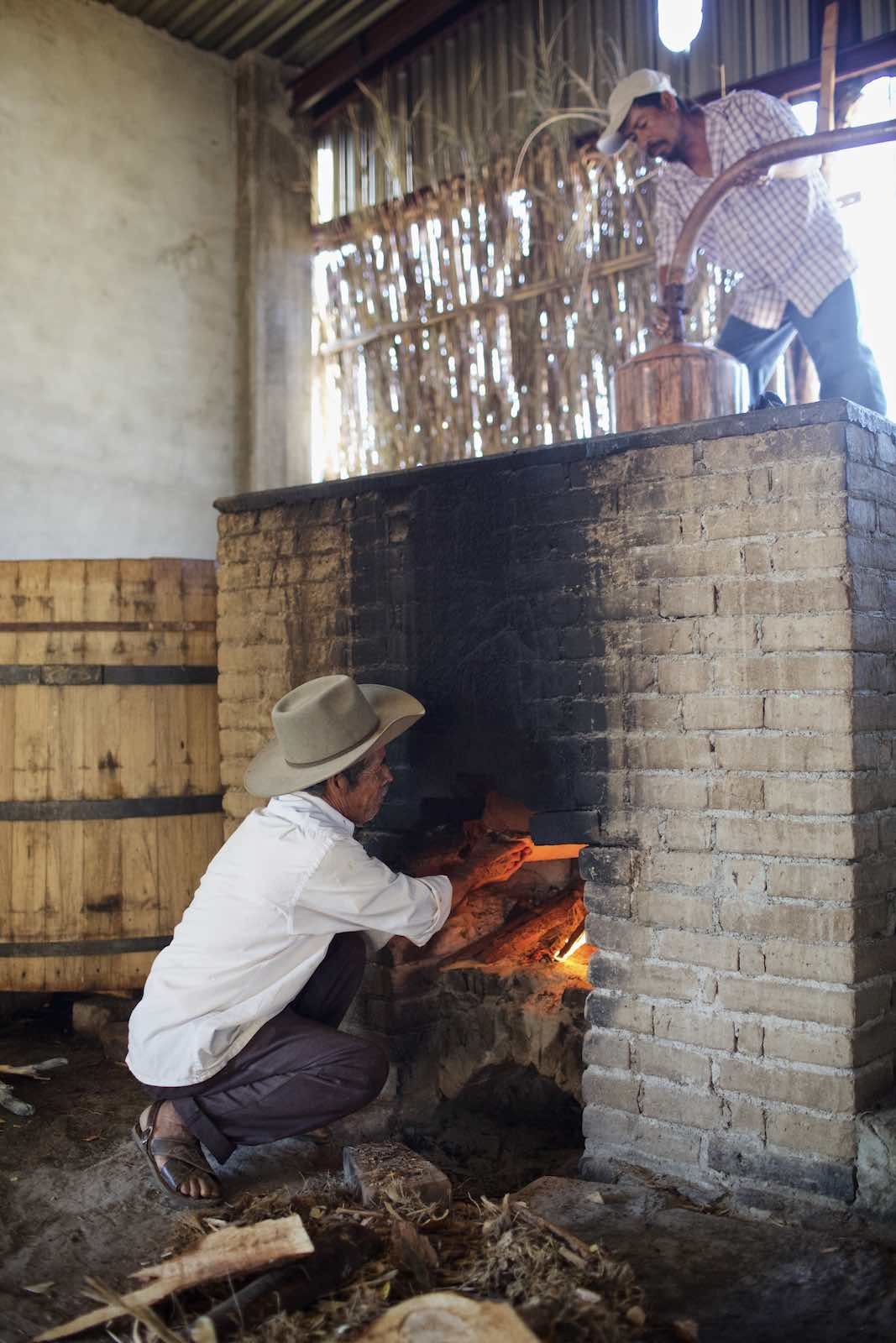 Jody Horton Photography - Farmer building a large fire within a brick oven.