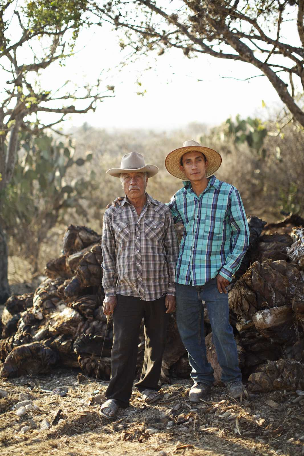 Two farmers during mezcal production.
