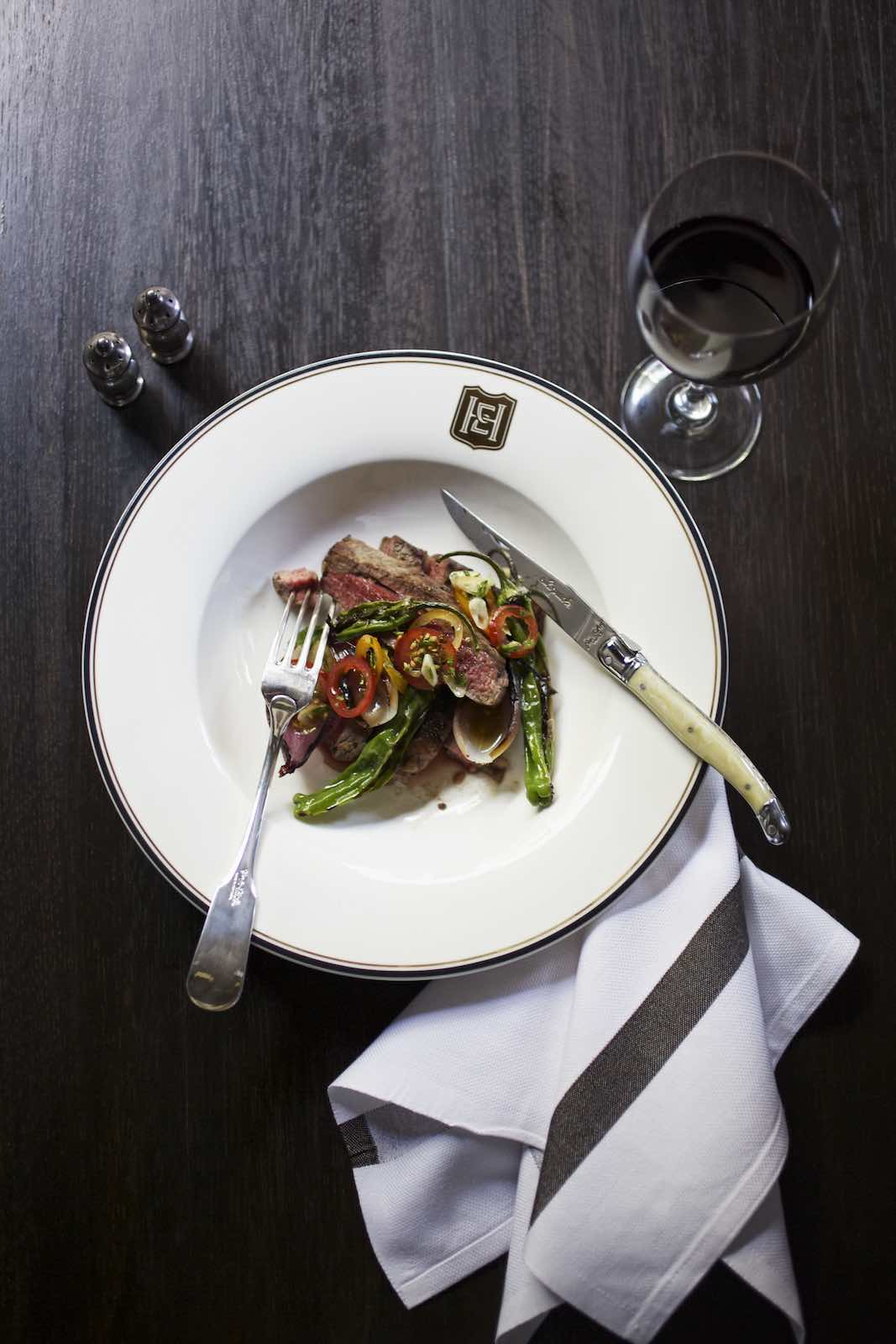 Jody Horton Photography - Steak dish in a monogrammed plate and red wine on a dark, wood table.