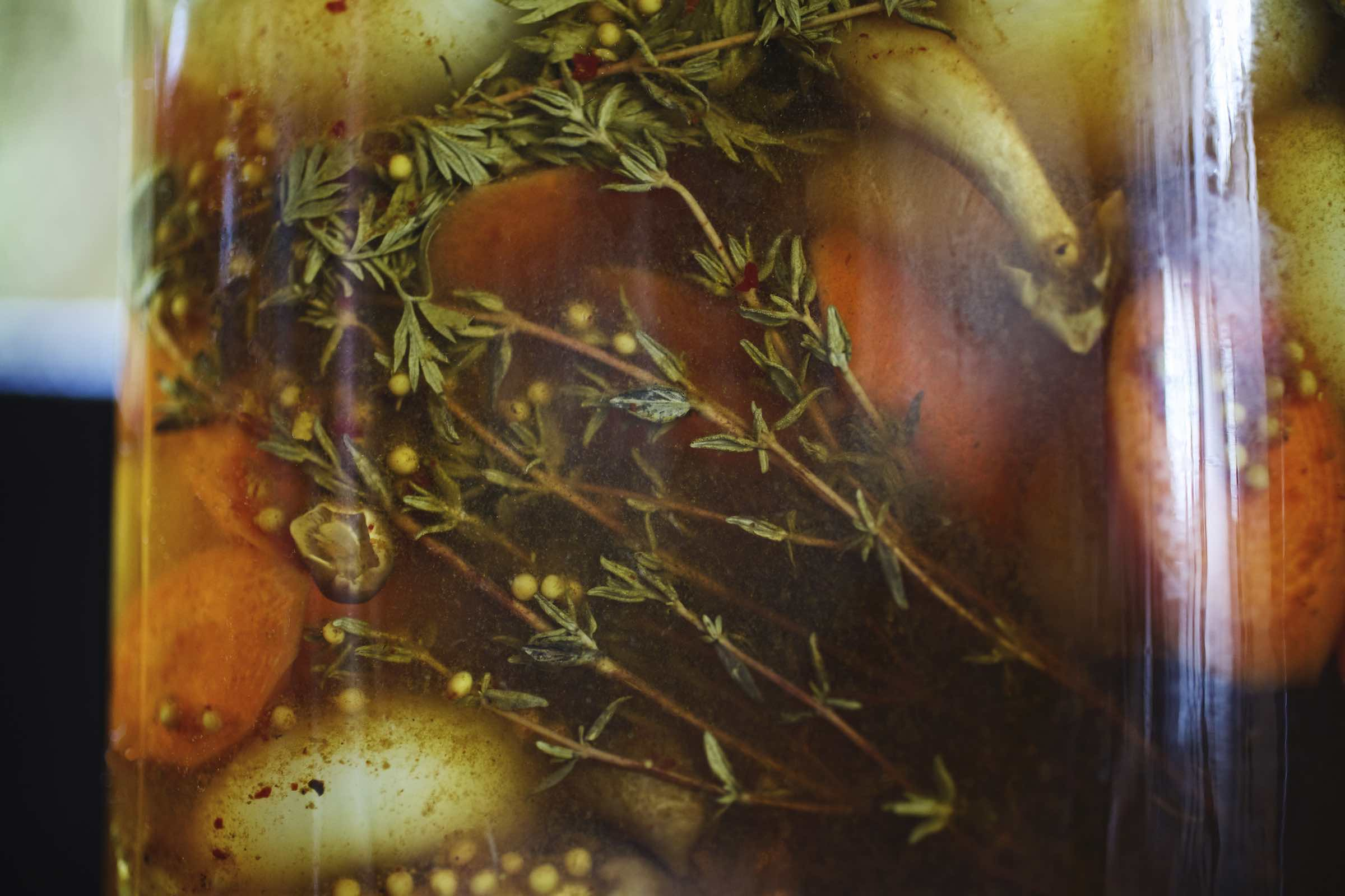 Jody Horton Photography - Herbs and vegetables pickling in a glass jar.