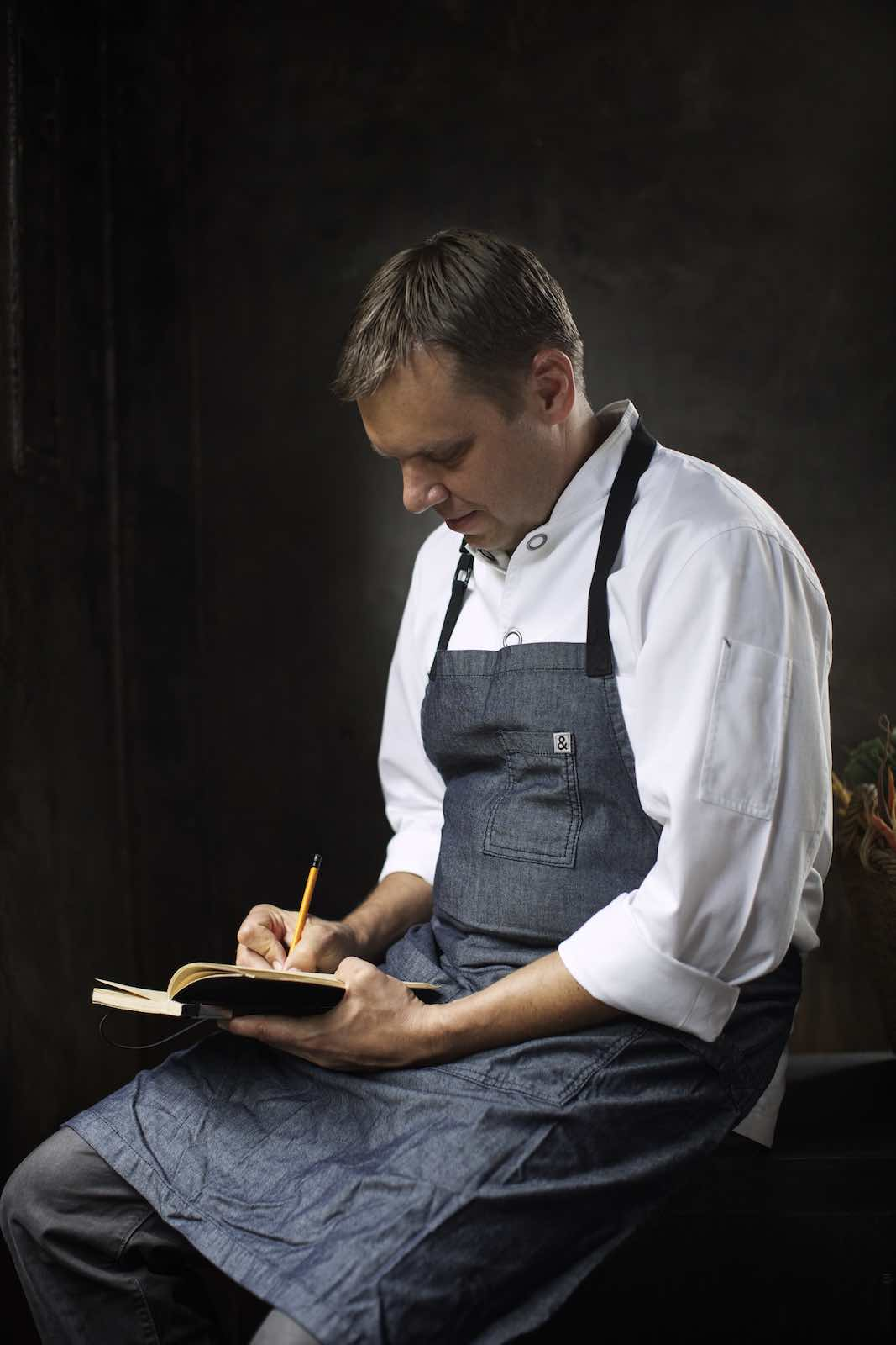 Jody Horton Photography - Chef in uniform recording in a notebook.
