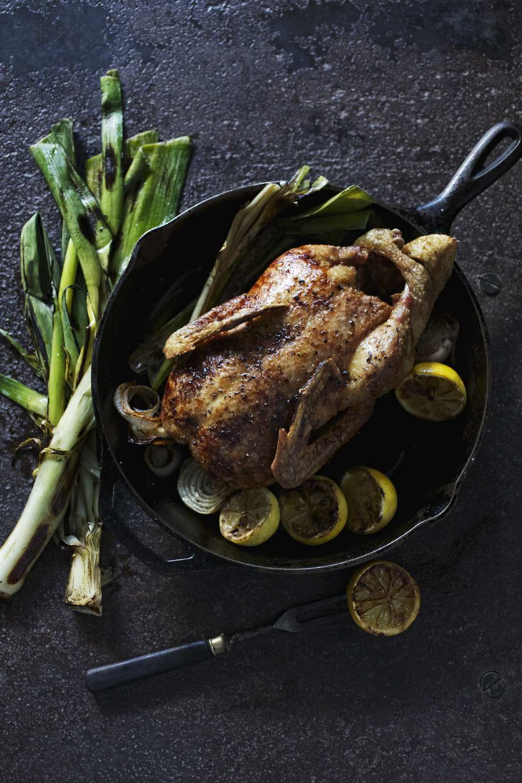 Jody Horton Photography - Roasted chicken with lemon and leaks in cast iron skillet.