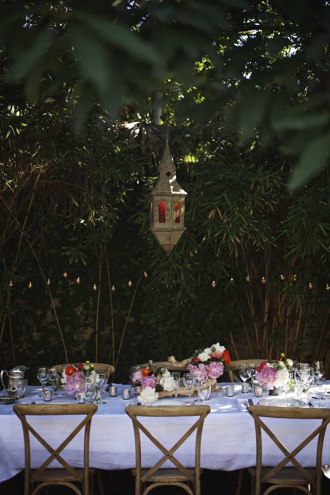 Jody Horton Photography - Floral, outdoor dinner table with bamboo and hanging lights.