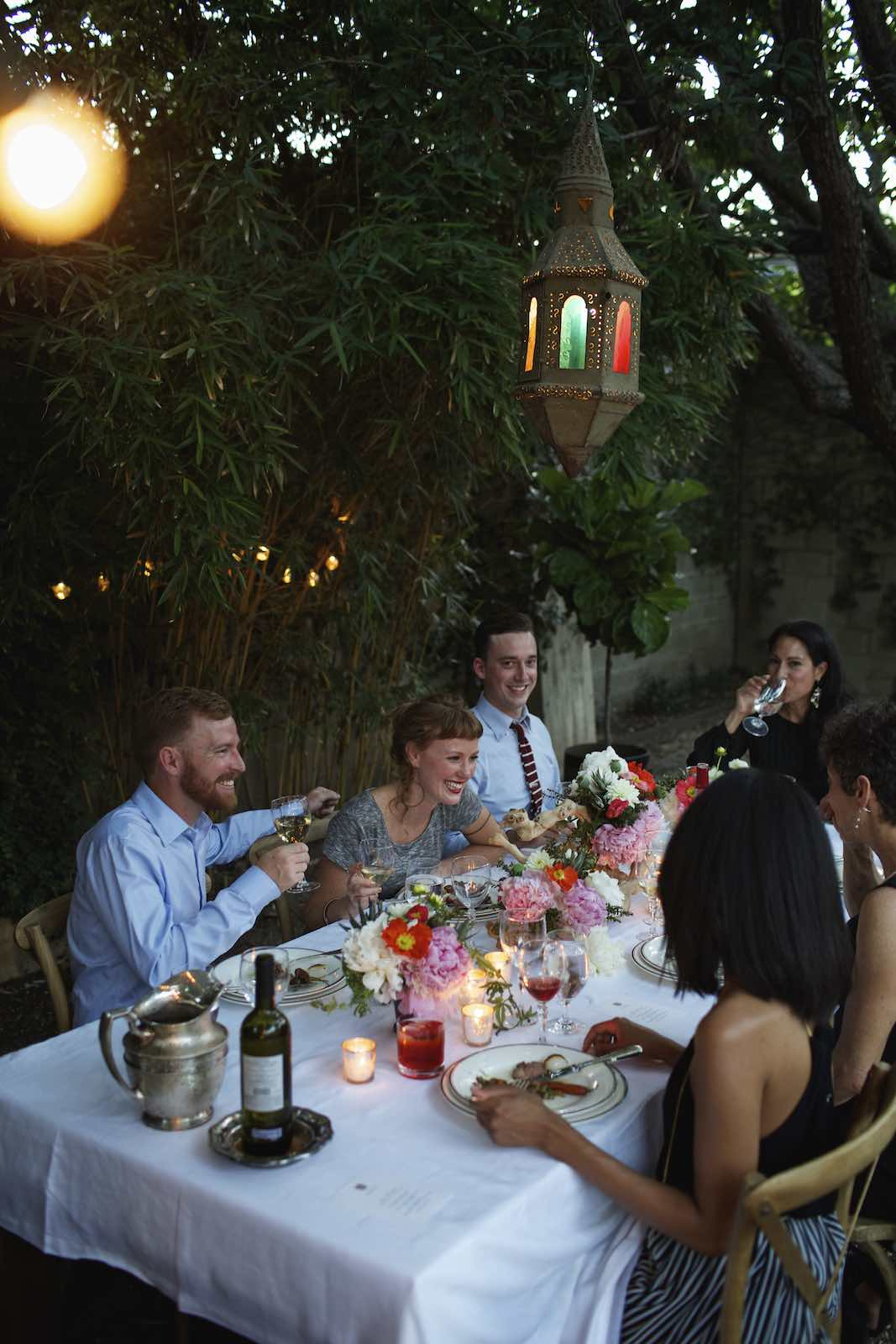 Jody Horton Photography - Candlelit dinner scene with friends laughing over wine.