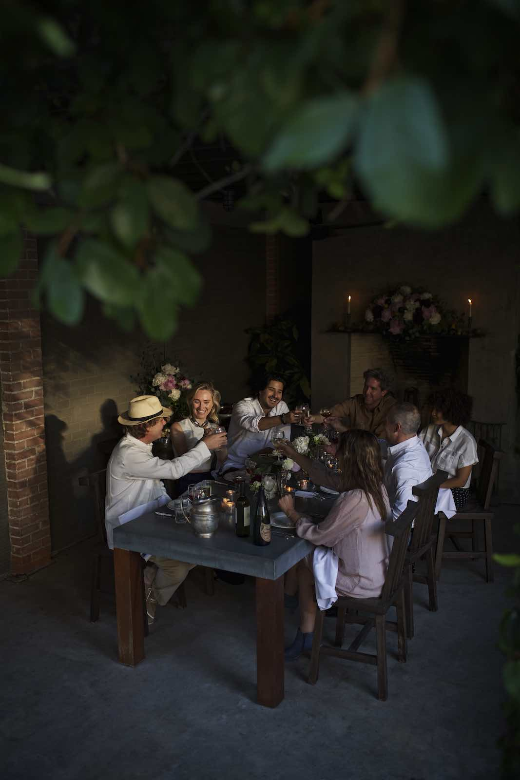 Jody Horton Photography - Evening dinner scene with friends cheersing at a stone table.
