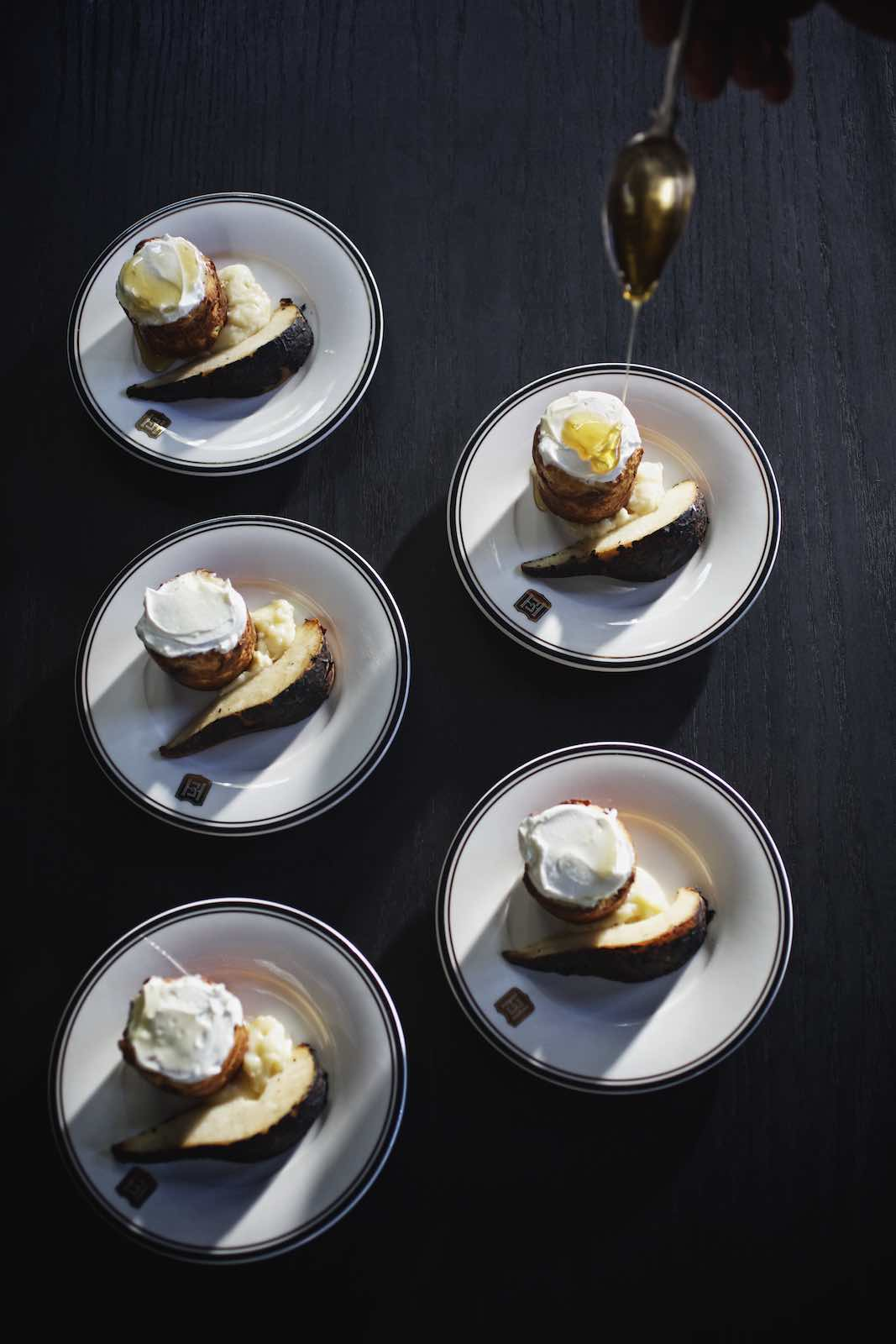 Jody Horton Photography - Delicate desserts drizzled with honey on a black table.