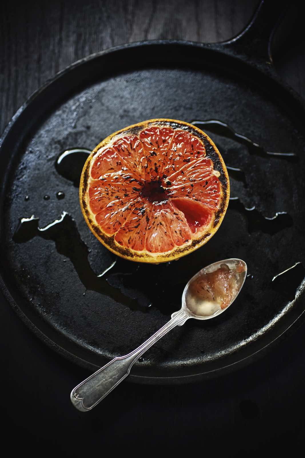 Jody Horton Photography - Halved grapefruit and silver spoon in a black skillet.