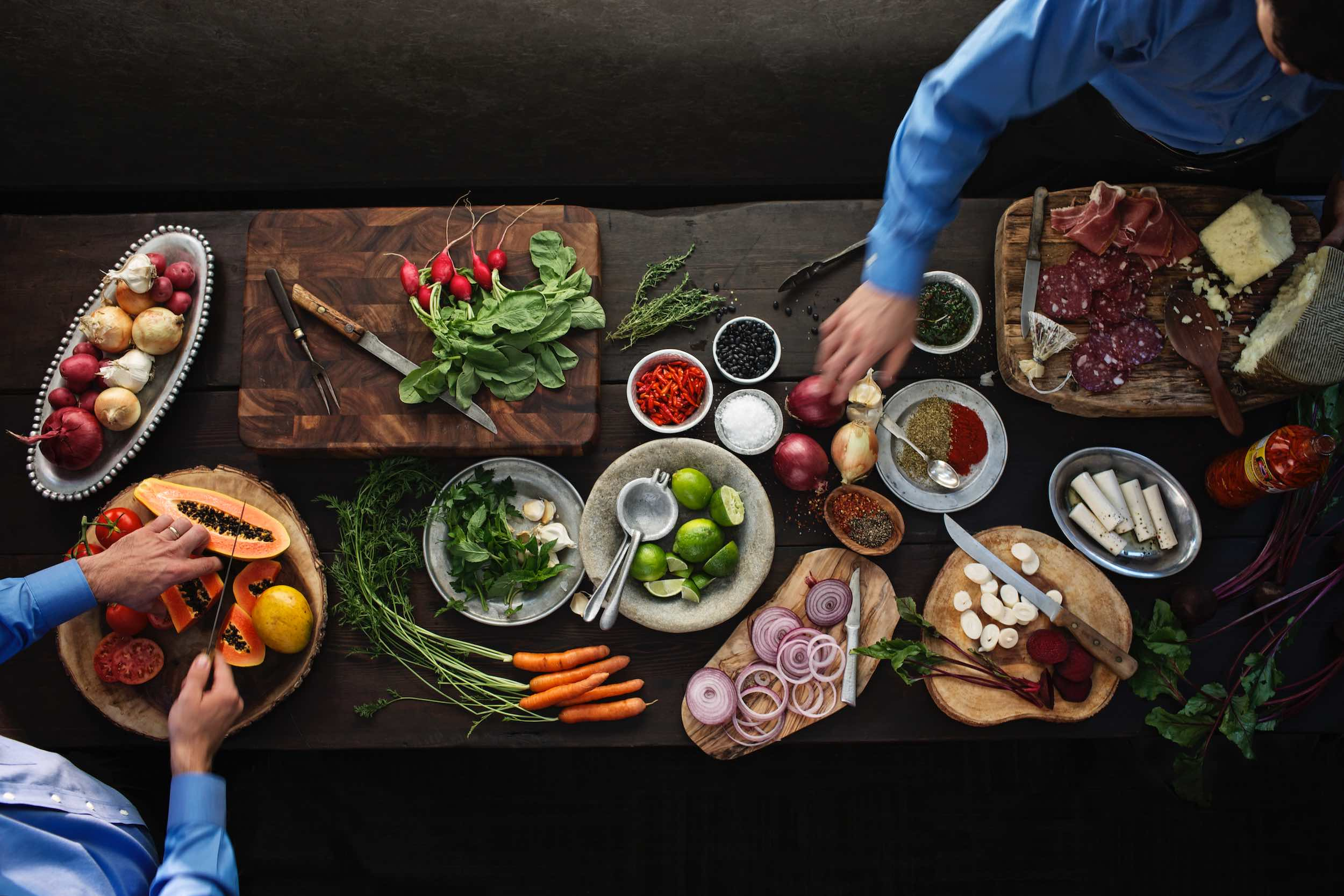 Jody Horton Photography - Cooks prepare ingredients on long wood table.