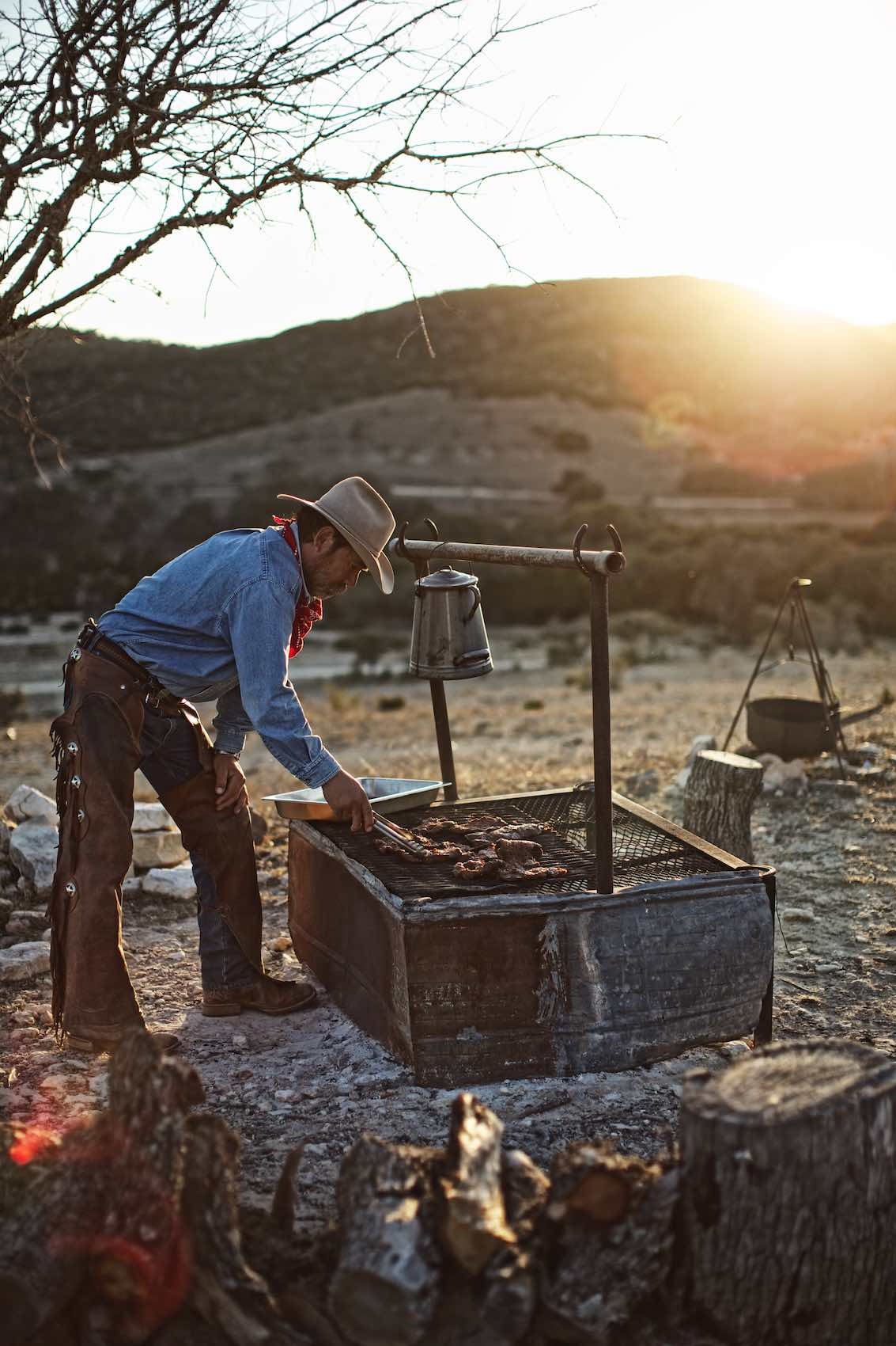Jody Horton Photography - Cowboy cooking meats on outdoor grill.