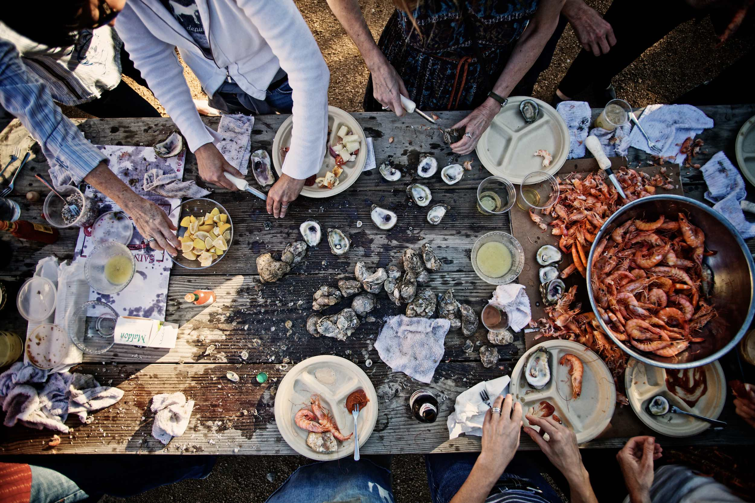 Jody Horton Photography - Oyster and shrimp preparation on wood picnic table.