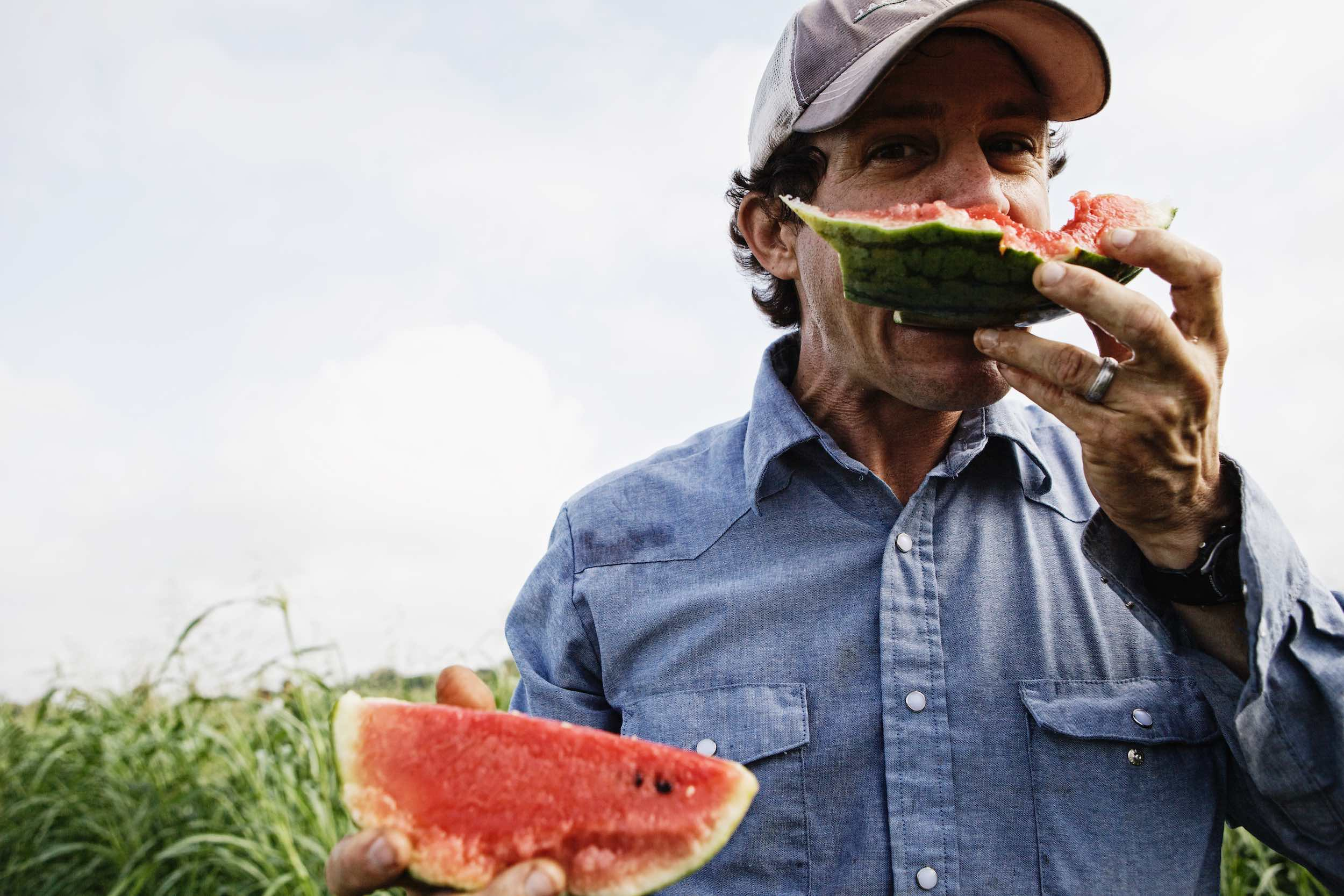 Jody Horton Photography - Farmer enjoying fresh watermelon outside.