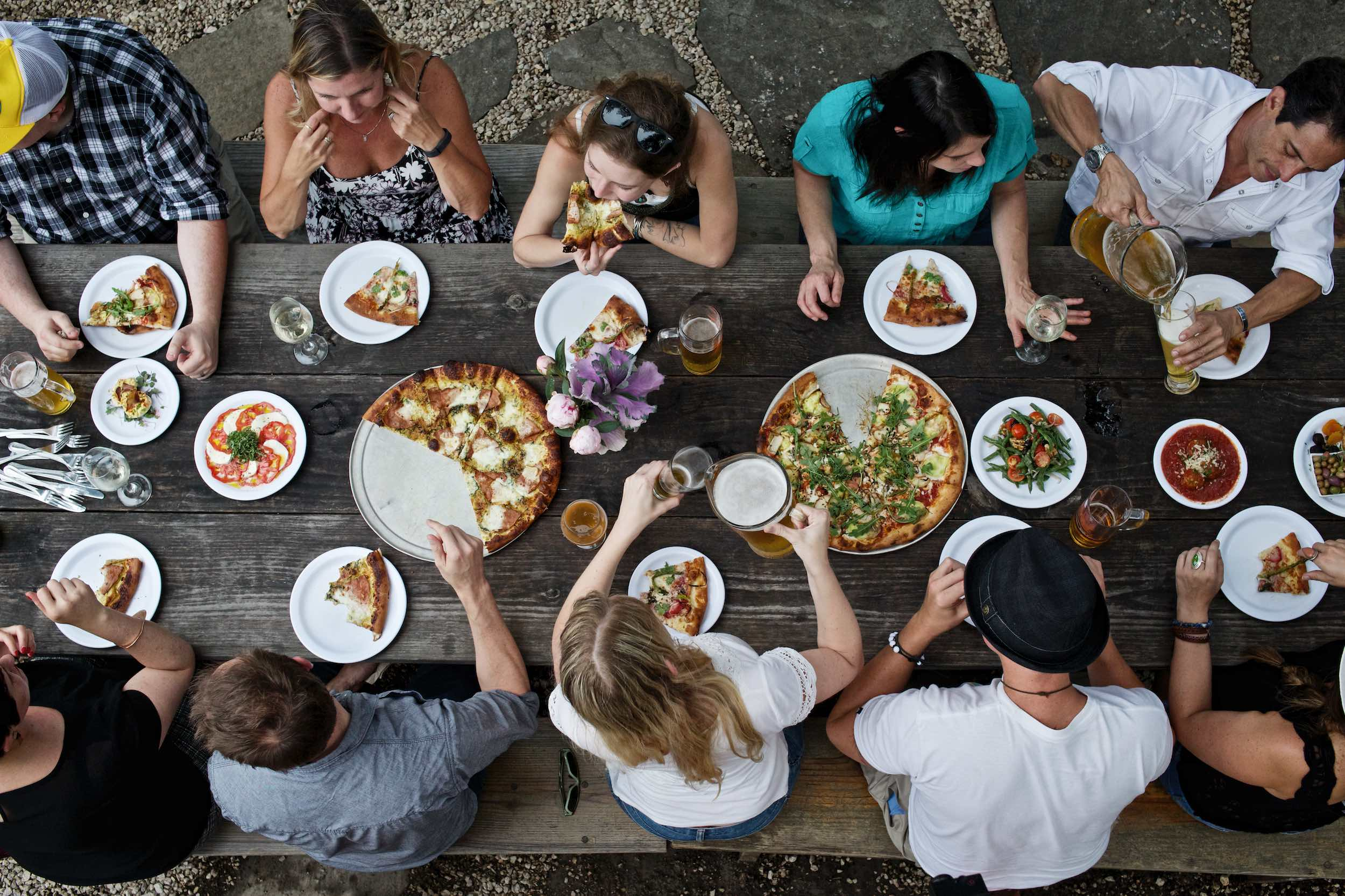 Jody Horton Photography - Friends gather around wood picnic table to eat pizza and drink beer.