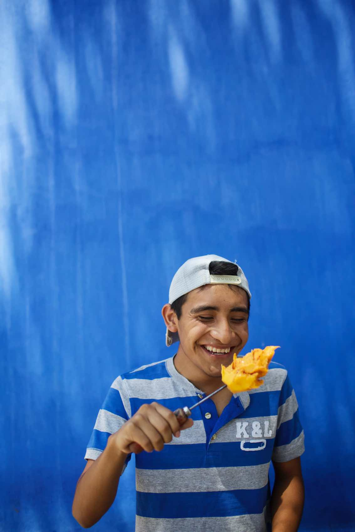 Jody Horton Photography - Young man eating mango off a skewer.