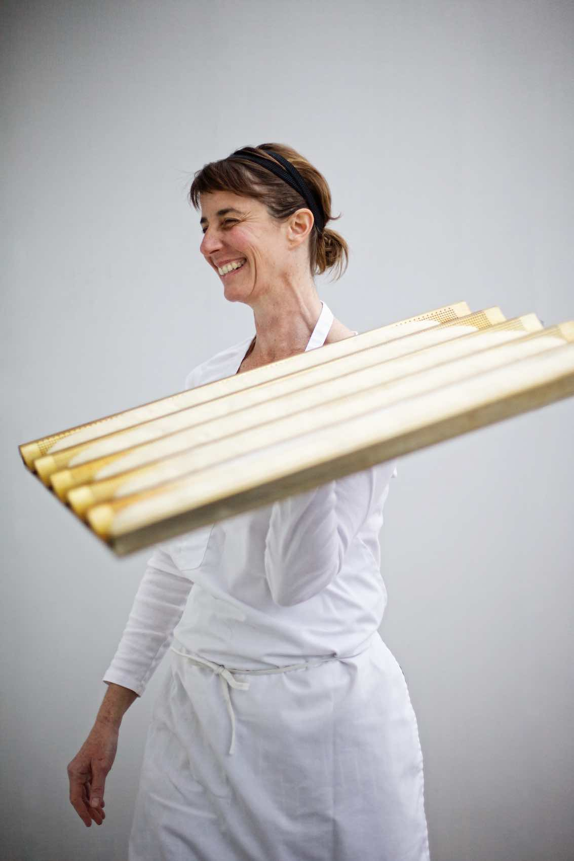 Jody Horton Photography - Baker in all white smiling, carrying a tray of unbaked baguettes.
