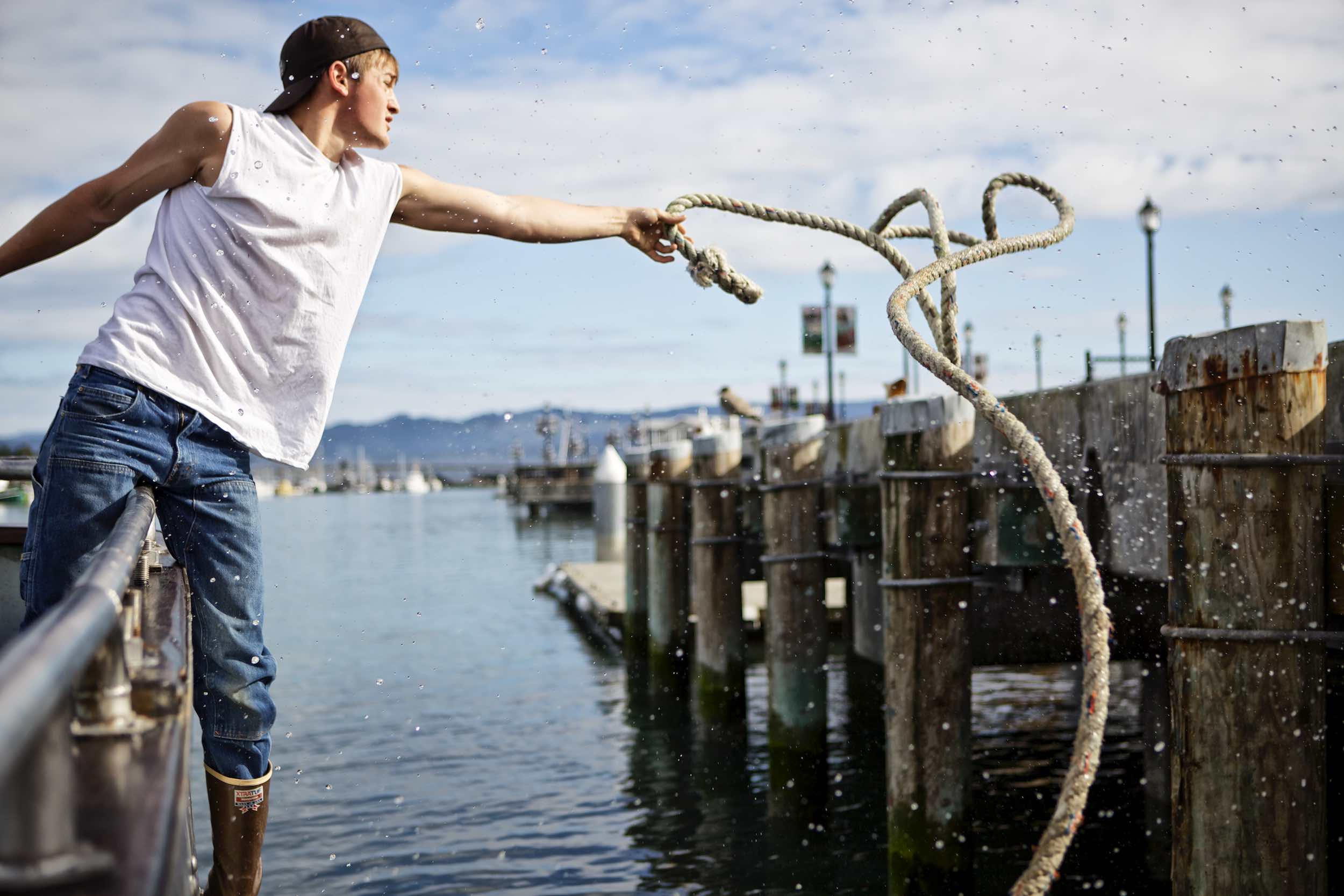 Jody Horton Photography - Fisherman casting rope from boat.