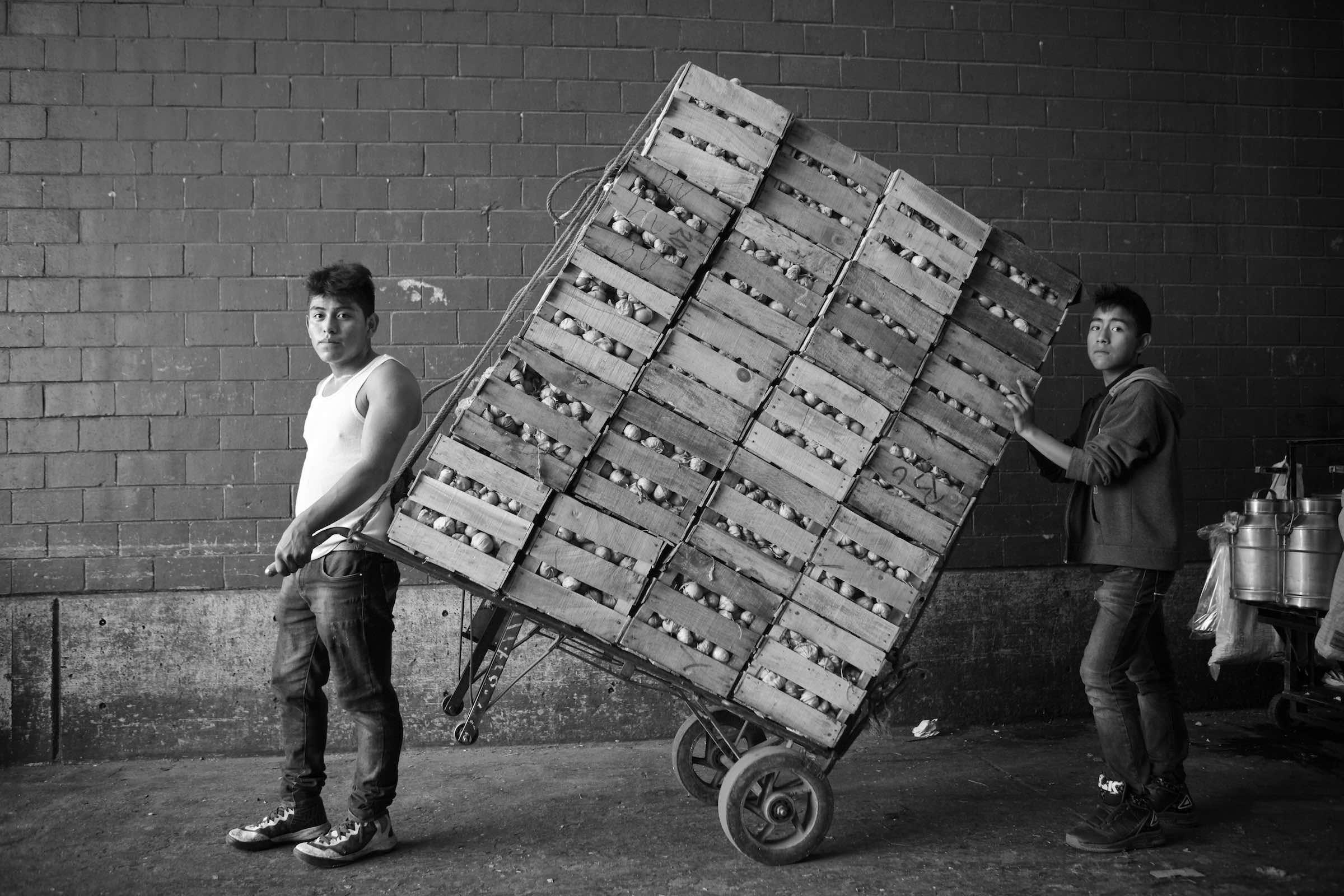 Jody Horton Photography - Young men hauling crates of produce together through the market, shot in B&W.