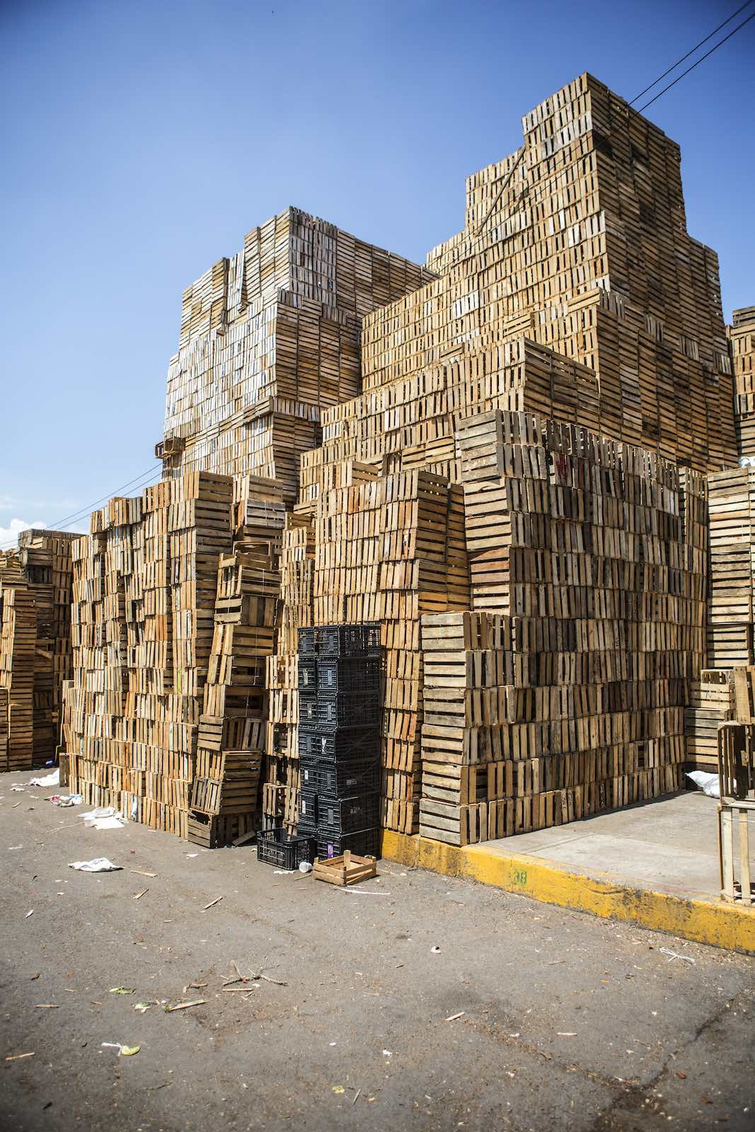 Wooden crates stacked stories high along a dusty street.