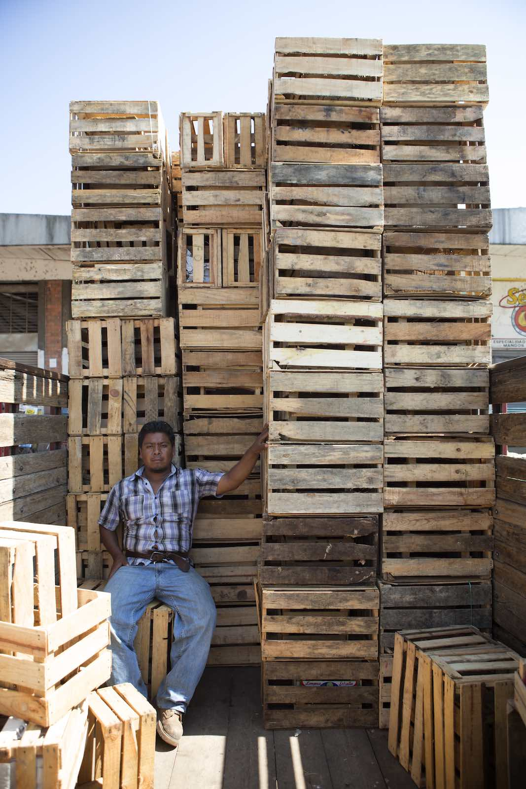 Man sitting in the shade of the stacks of empty crates.