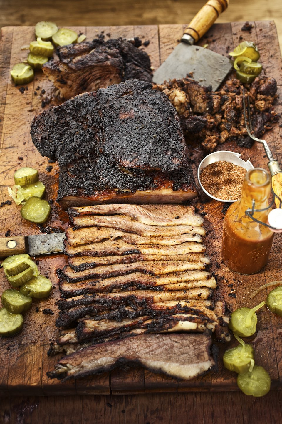 Half carved brisket with pickles and barbecue sauce on a wood cutting board.