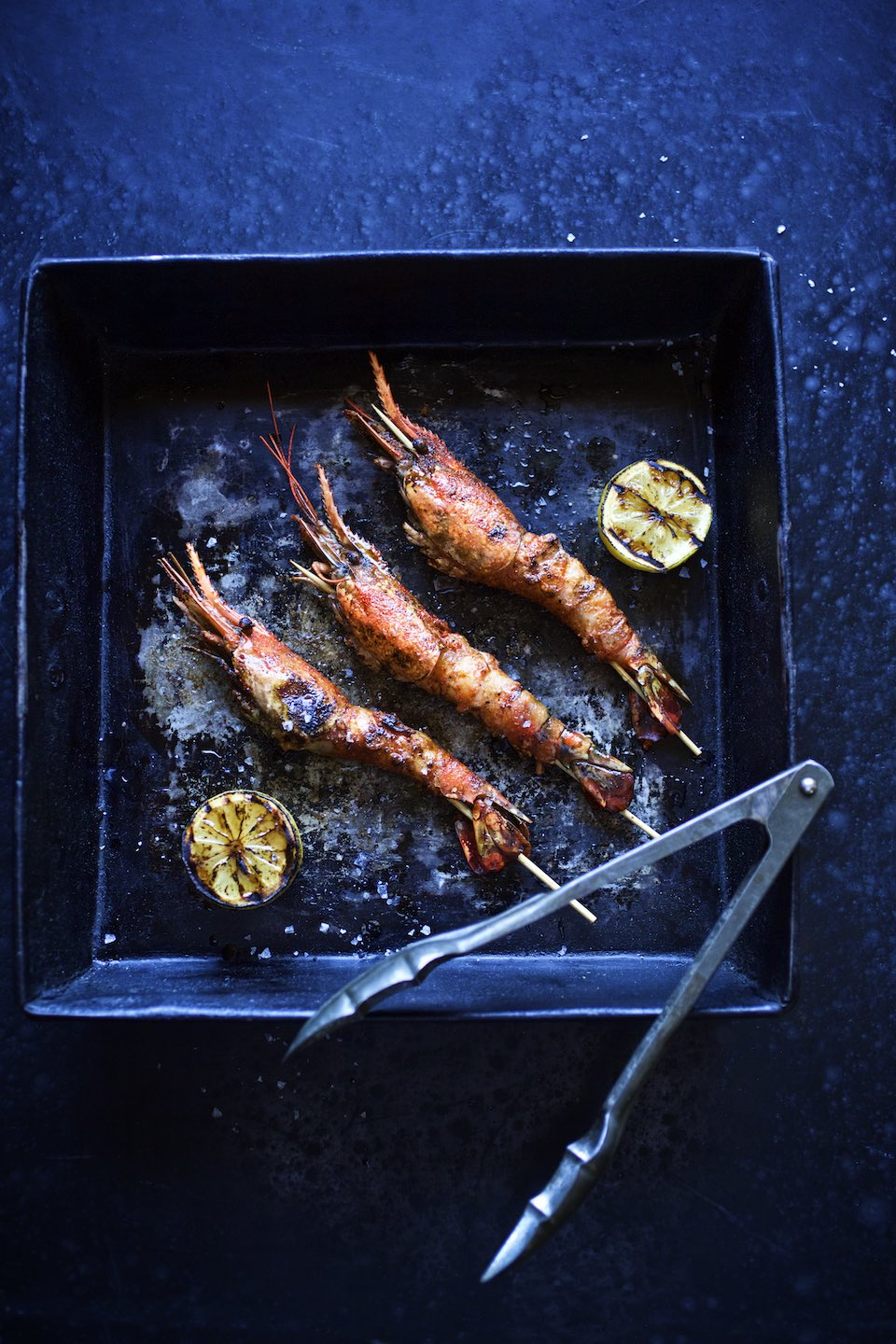 Three skewered prawns with lemon in cast iron, on black surface.