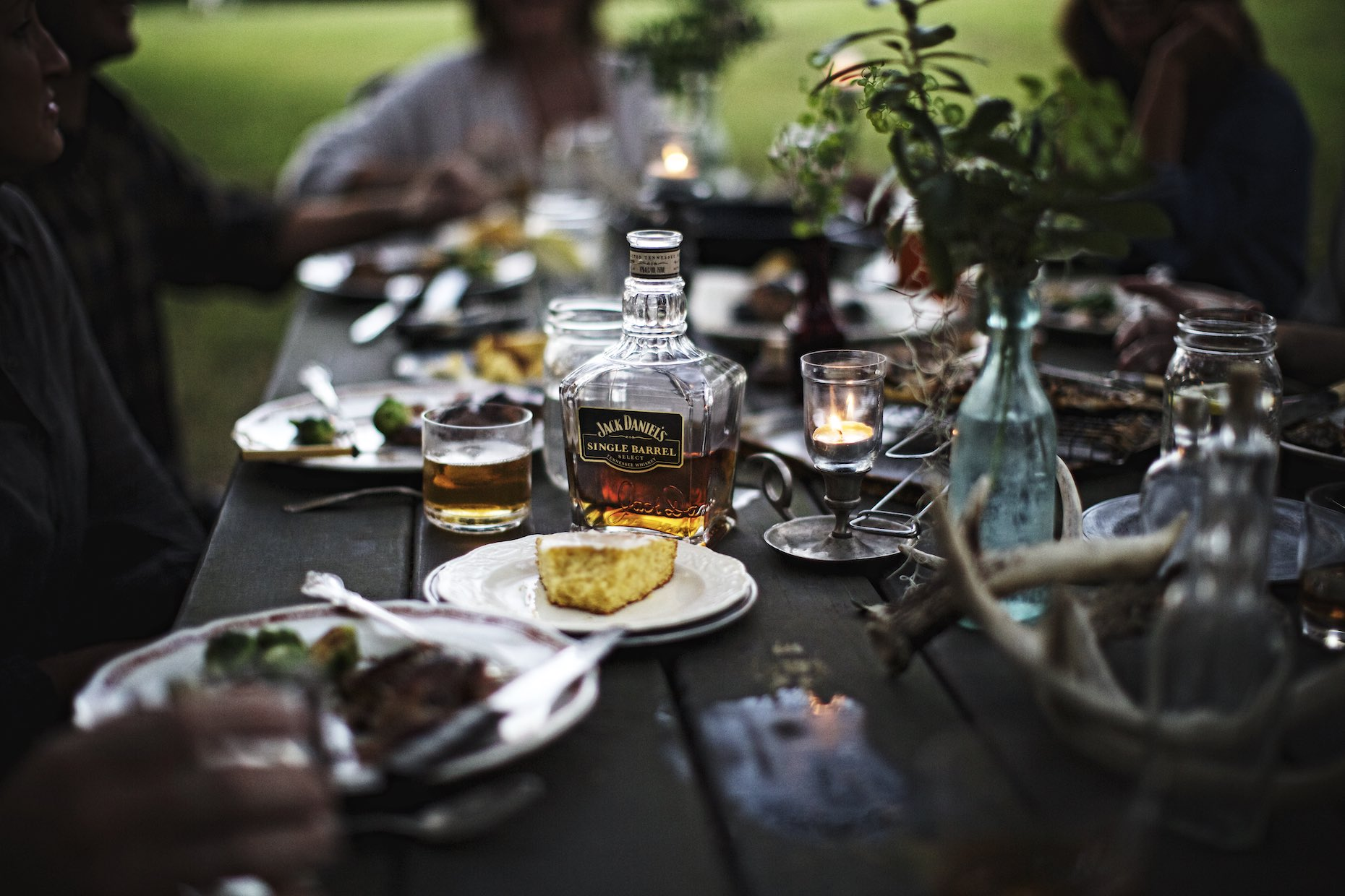 Outdoor, candlelit dinner spread with Jack Daniel