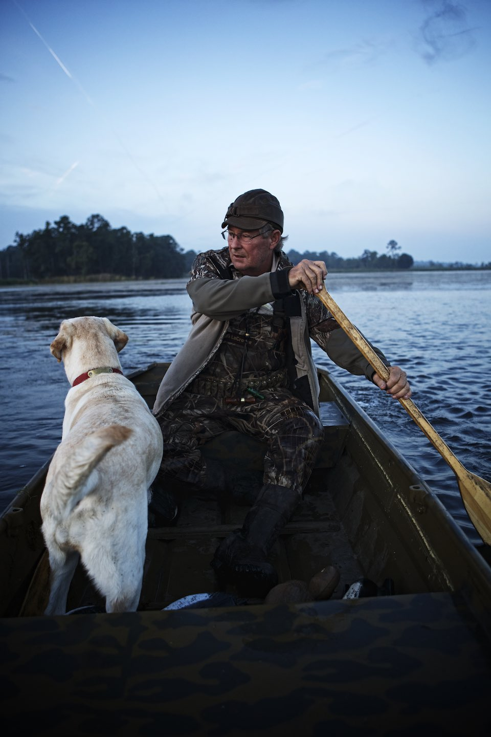 Man and his dog canoeing on a lake at evening time.