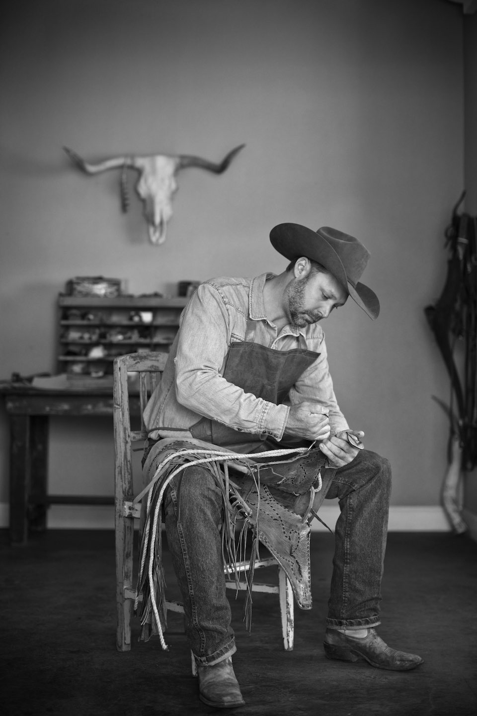 Leather worker sitting on a wood chair working on a piece, shot in B&W.