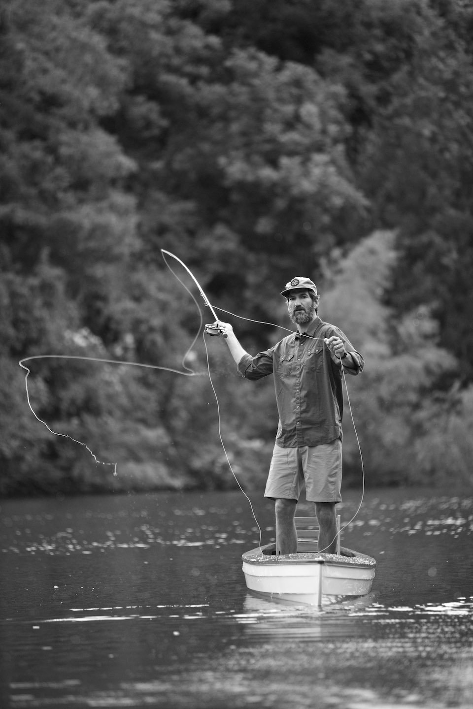 Fisherman standing in a small boat while casting a line, shot in B&W.