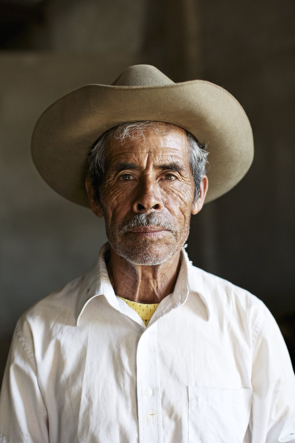 Portrait of mezcal farmer in a white button down and brown hat.