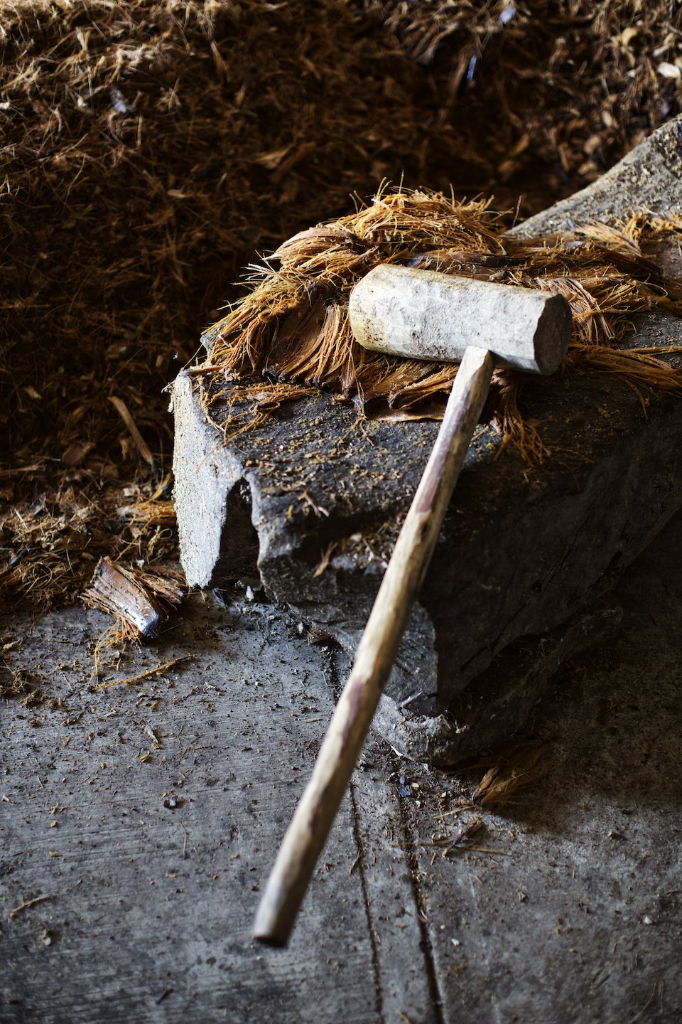 Wooden mallet and agave fibers during mezcal production.
