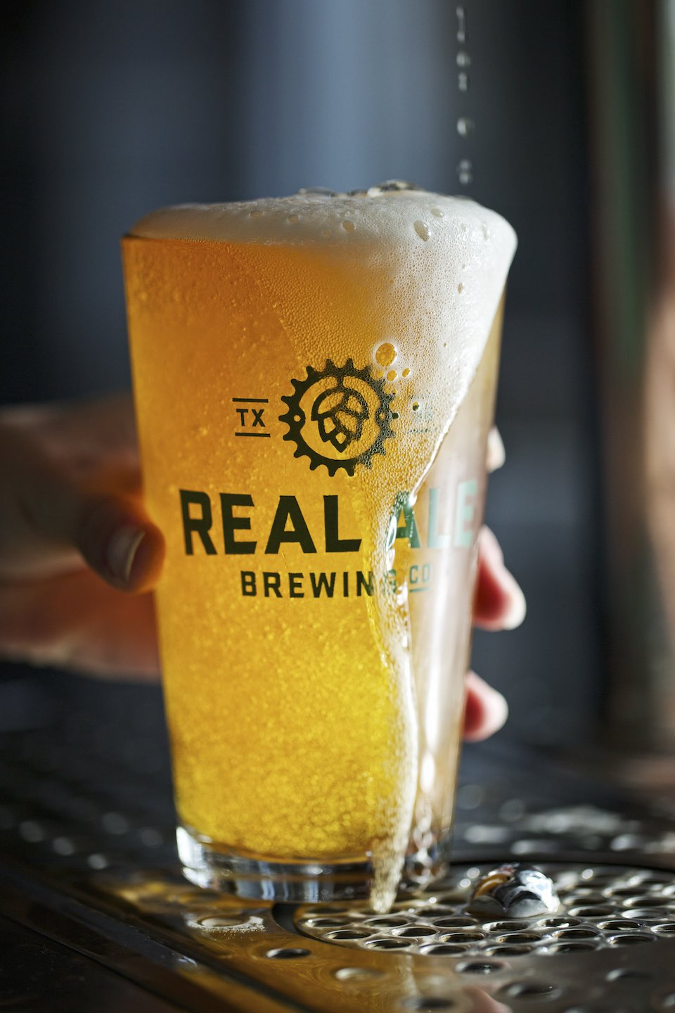 A light beer being poured on draft into a Real Ale Brewing Co. glass.