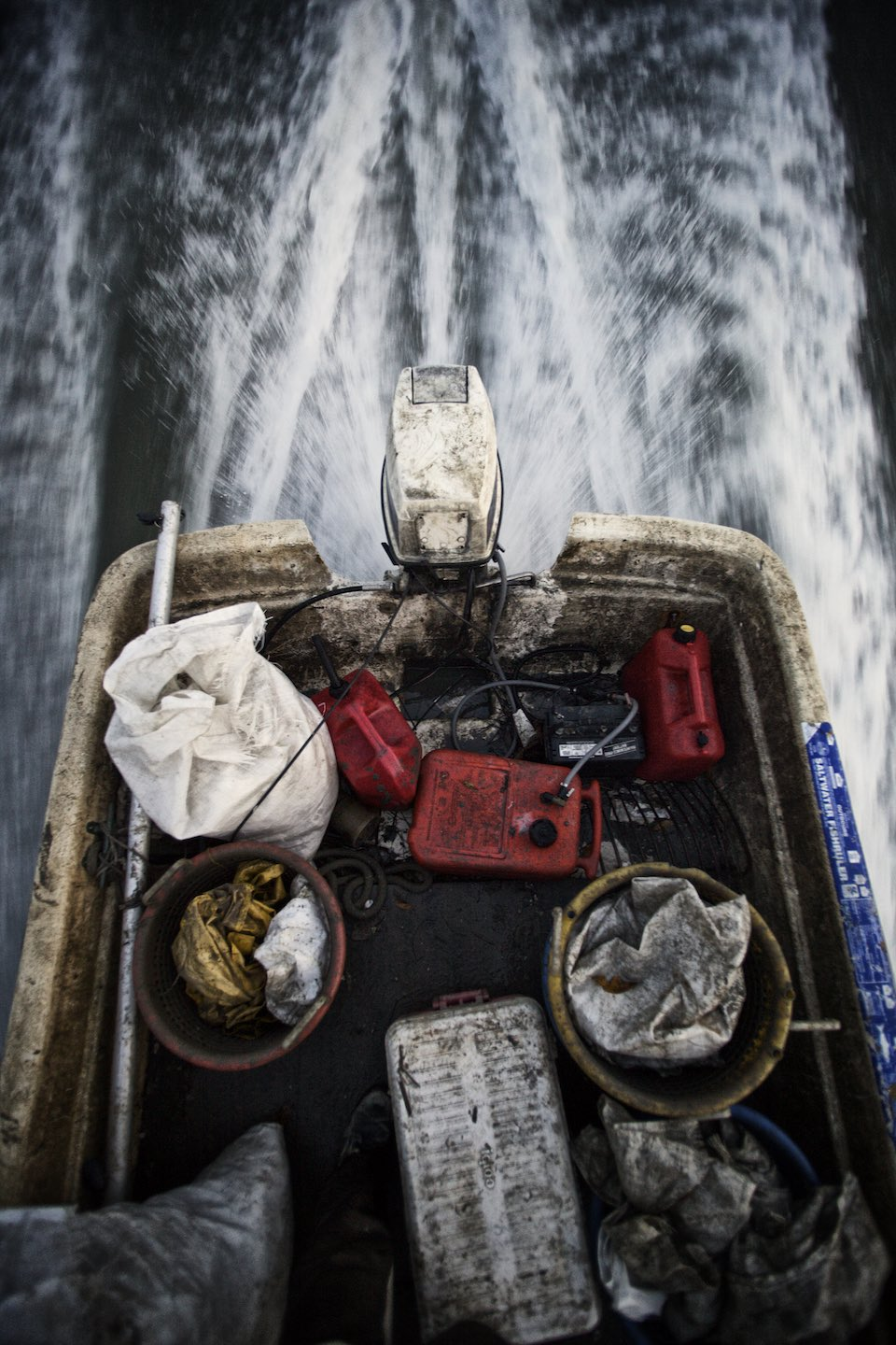 Motor boat carrying  fishing gear on the water.