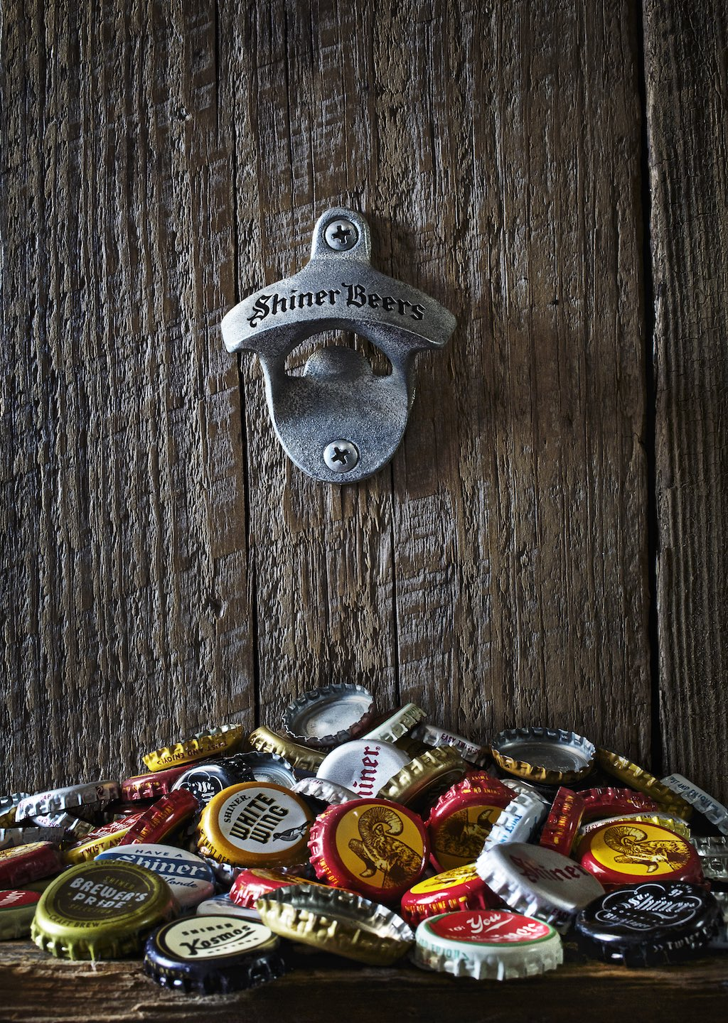 Bottle opener and various beer caps against a wood wall.