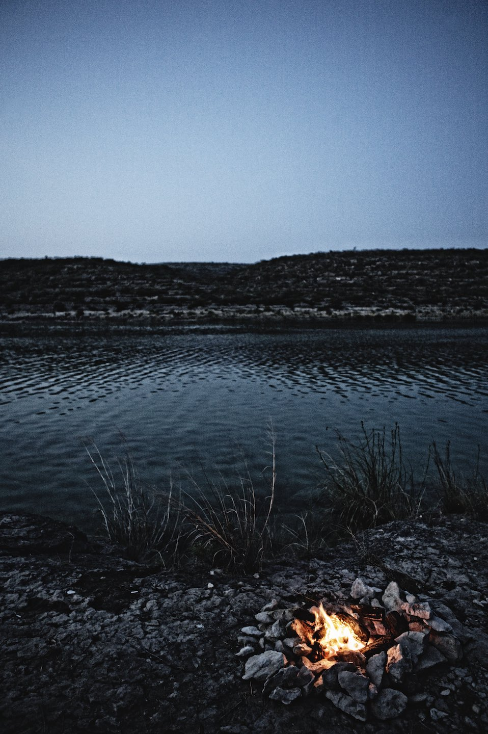 A small camp fire blazing next to a calm river at dusk.